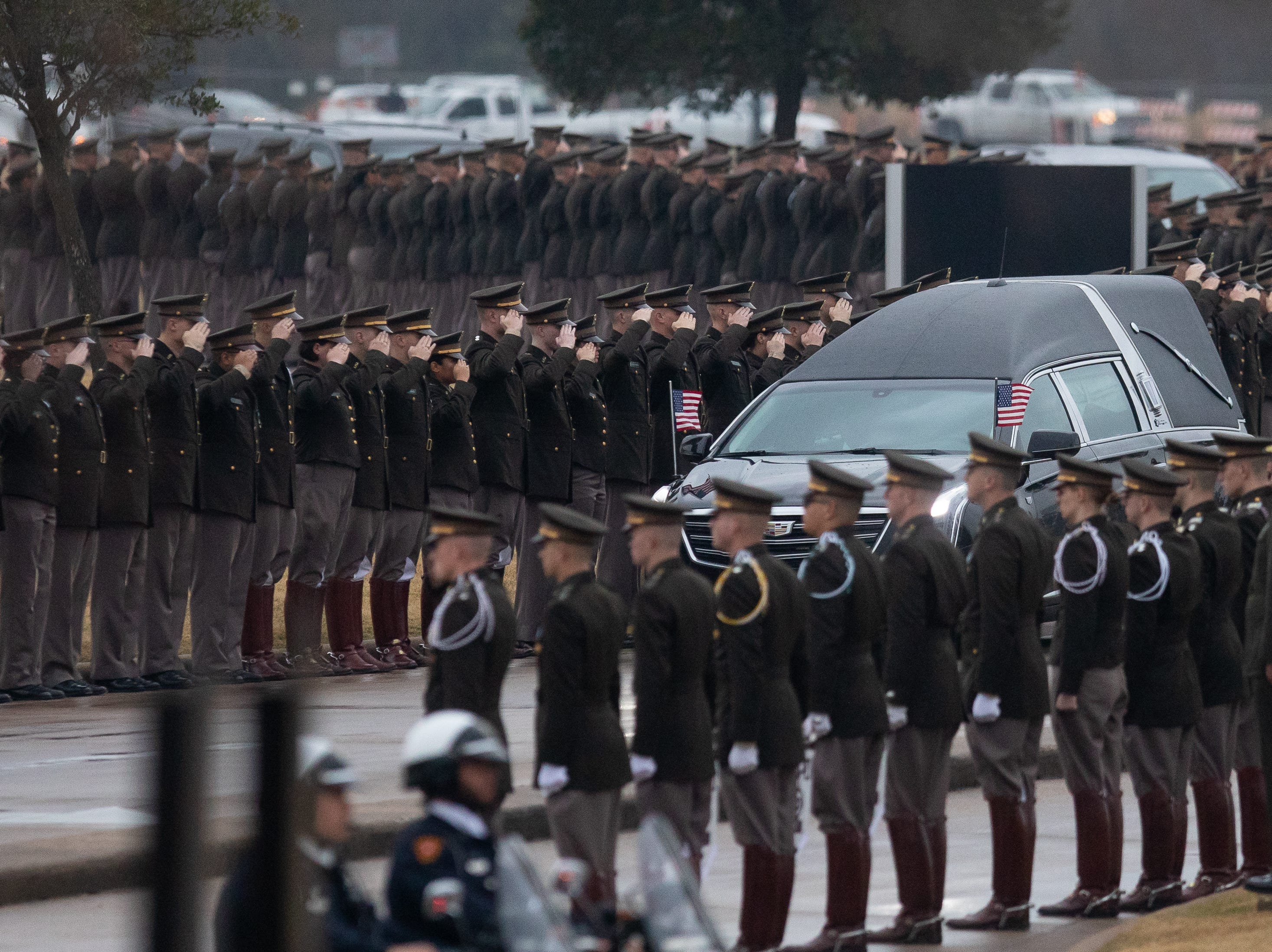 Members of the Texas A&M Corps of Cadets salute the hearse carrying George H.W. Bush as it arrives at the George Bush Presidential Library & Museum in College Station on Thursday, Dec 6, 2018.