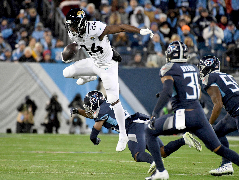 Jacksonville Jaguars running back T.J. Yeldon (24) leaps over Tennessee Titans cornerback LeShaun Sims (36) during the first half at Nissan Stadium.