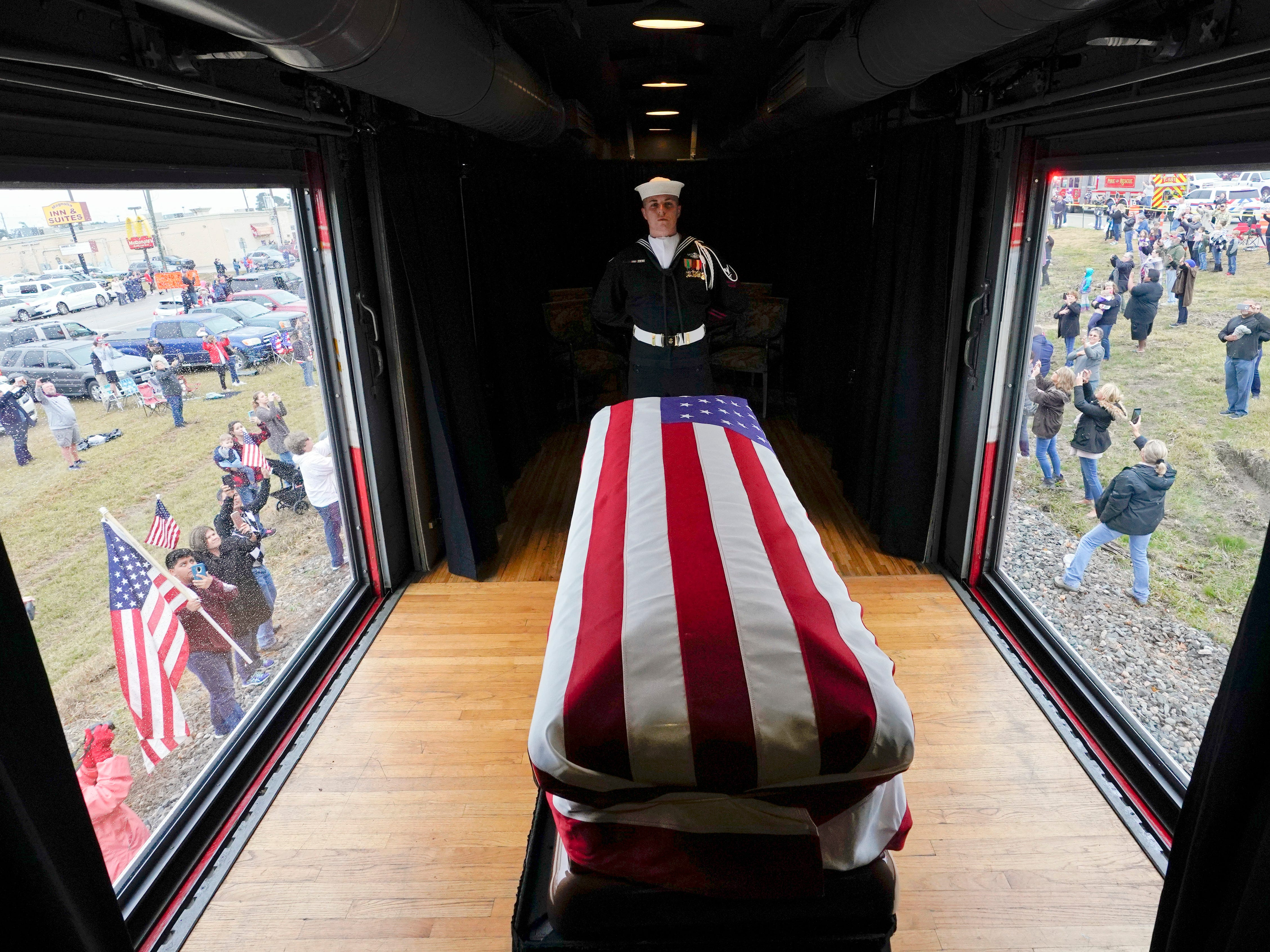 The flag-draped casket of former President George H.W. Bush passes through Magnolia, Texas, Thursday, Dec. 6, 2018, along the route from Spring to College Station, Texas.