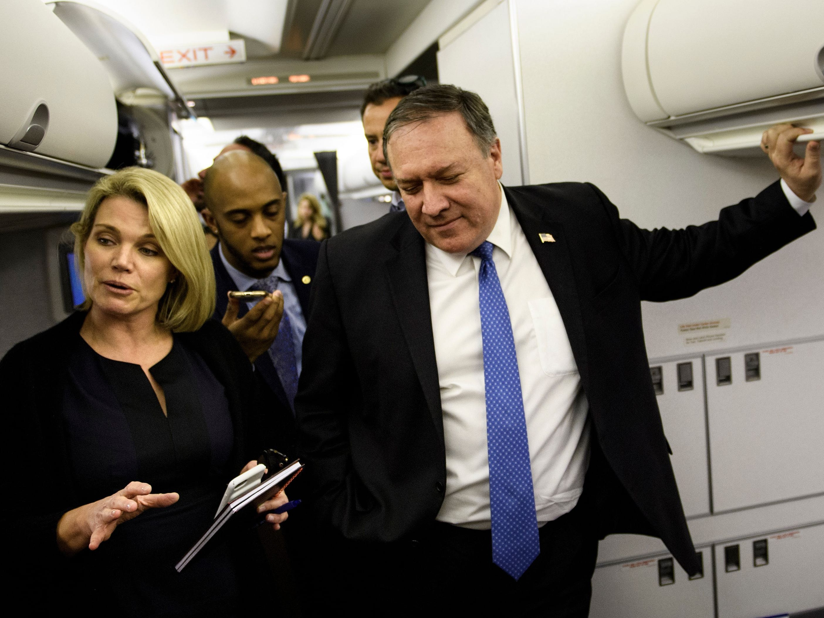 State Department spokesperson Heather Nauert, left, listens while Secretary of State Mike Pompeo speaks with reporters in his plane while flying from Panama to Mexico on Oct. 18, 2018.