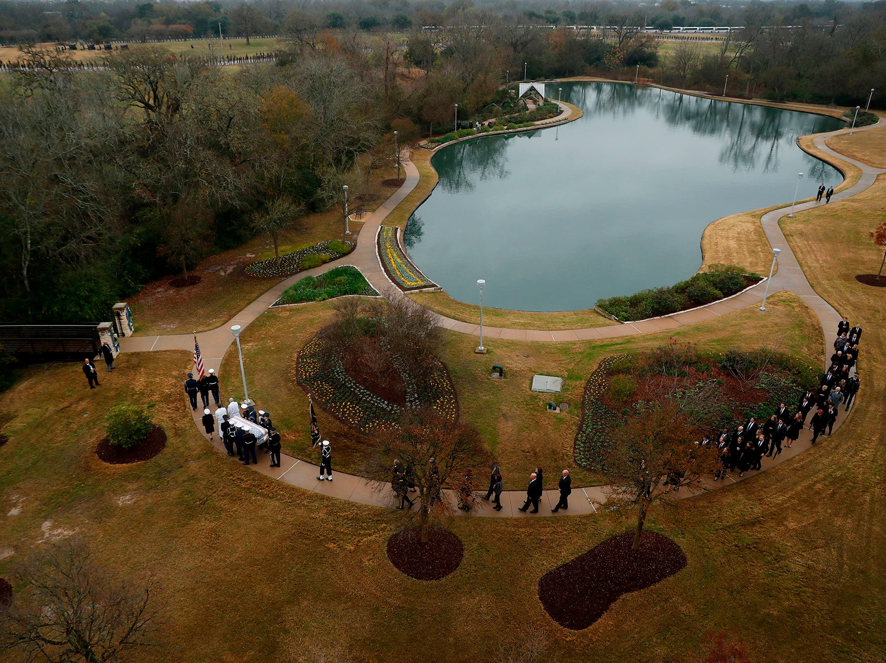The flag-draped casket of former President George H.W. Bush is carried by a joint services military honor guard followed by family members at the George H.W. Bush Presidential Library and Museum Thursday, Dec. 6, 2018, in College Station, Texas.