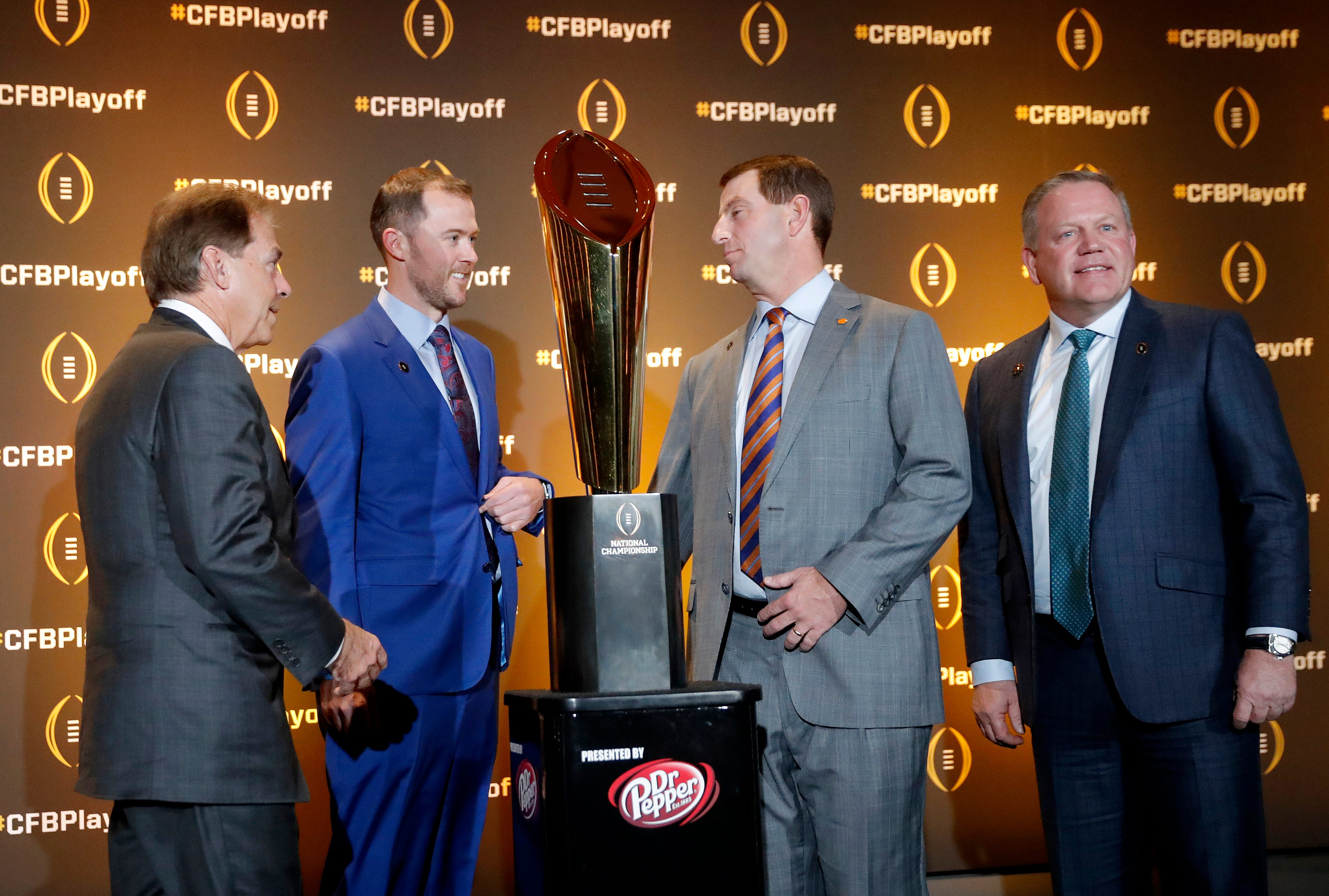 The coaches of the four teams in the College Football Playoff, Alabama's Nick Saban, Oklahoma's Lincoln Riley, Clemson's Dabo Swinney and Notre Dame's Brian Kelly chat after a news conference in Atlanta.