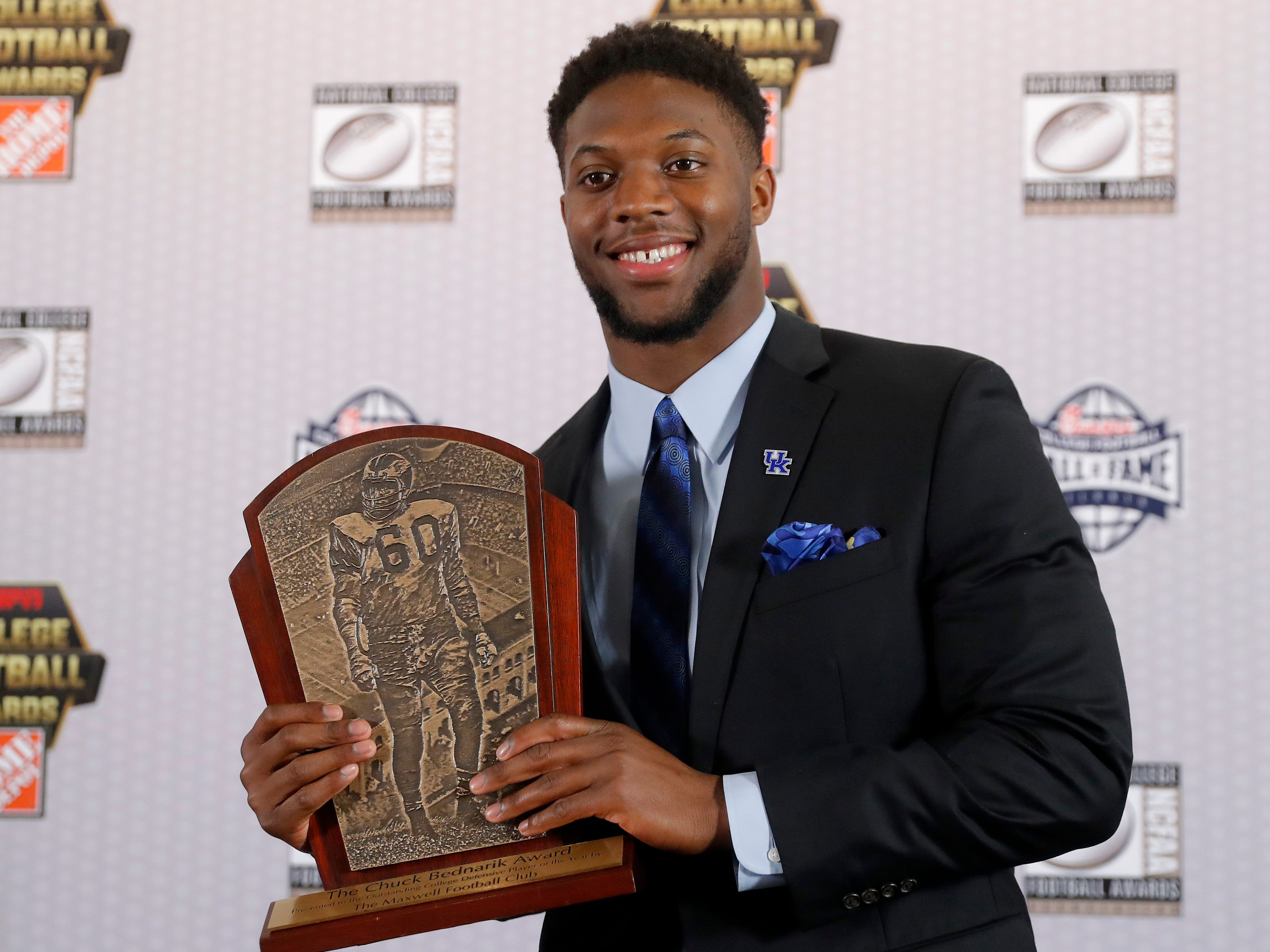 Kentucky's Josh Allen poses with the trophy after winning the Chuck Bednarik Award as college football's top defensive player of the year.