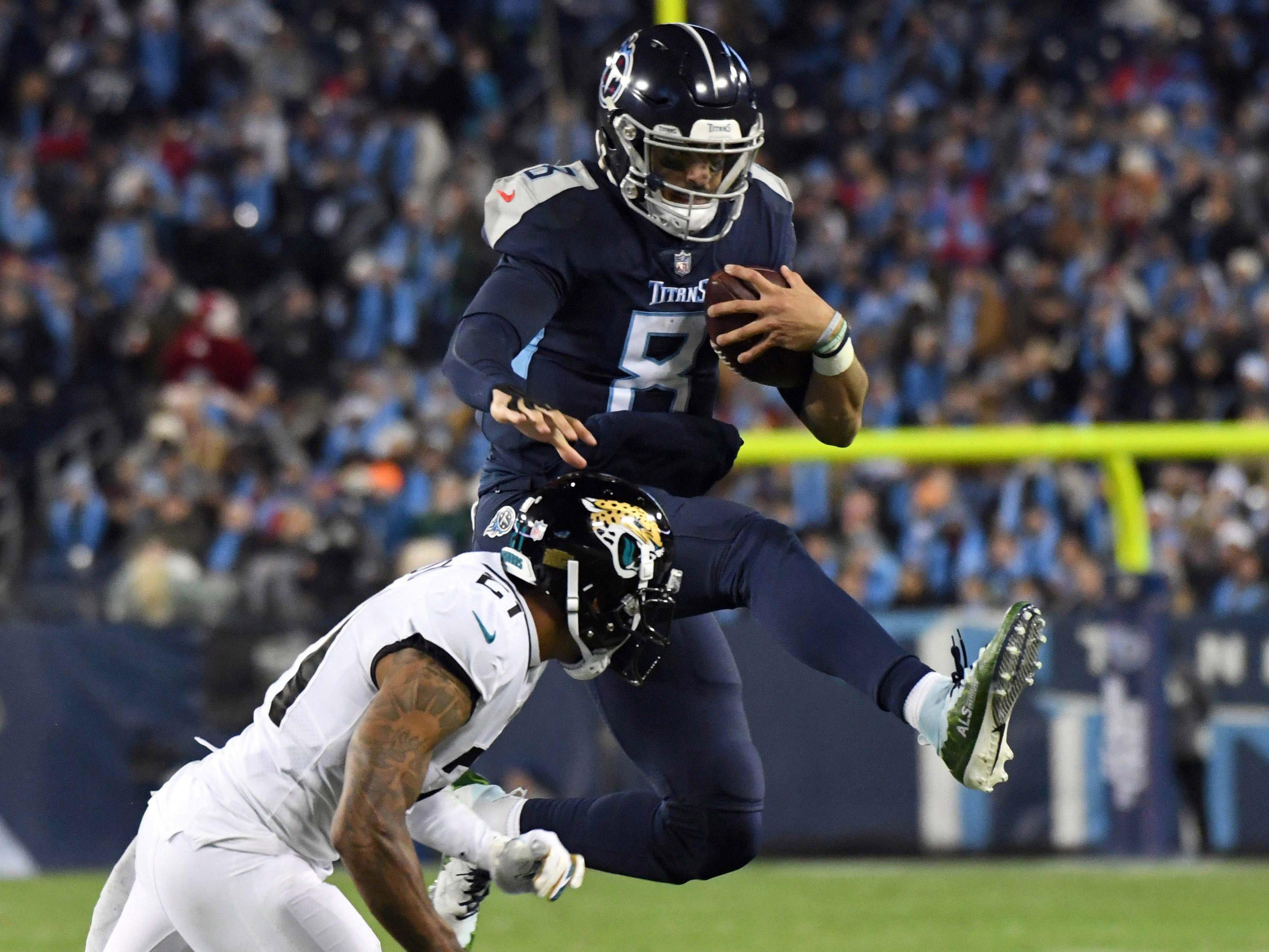 Tennessee Titans quarterback Marcus Mariota leaps over Jacksonville Jaguars cornerback A.J. Bouye in the third quarter at Nissan Stadium.