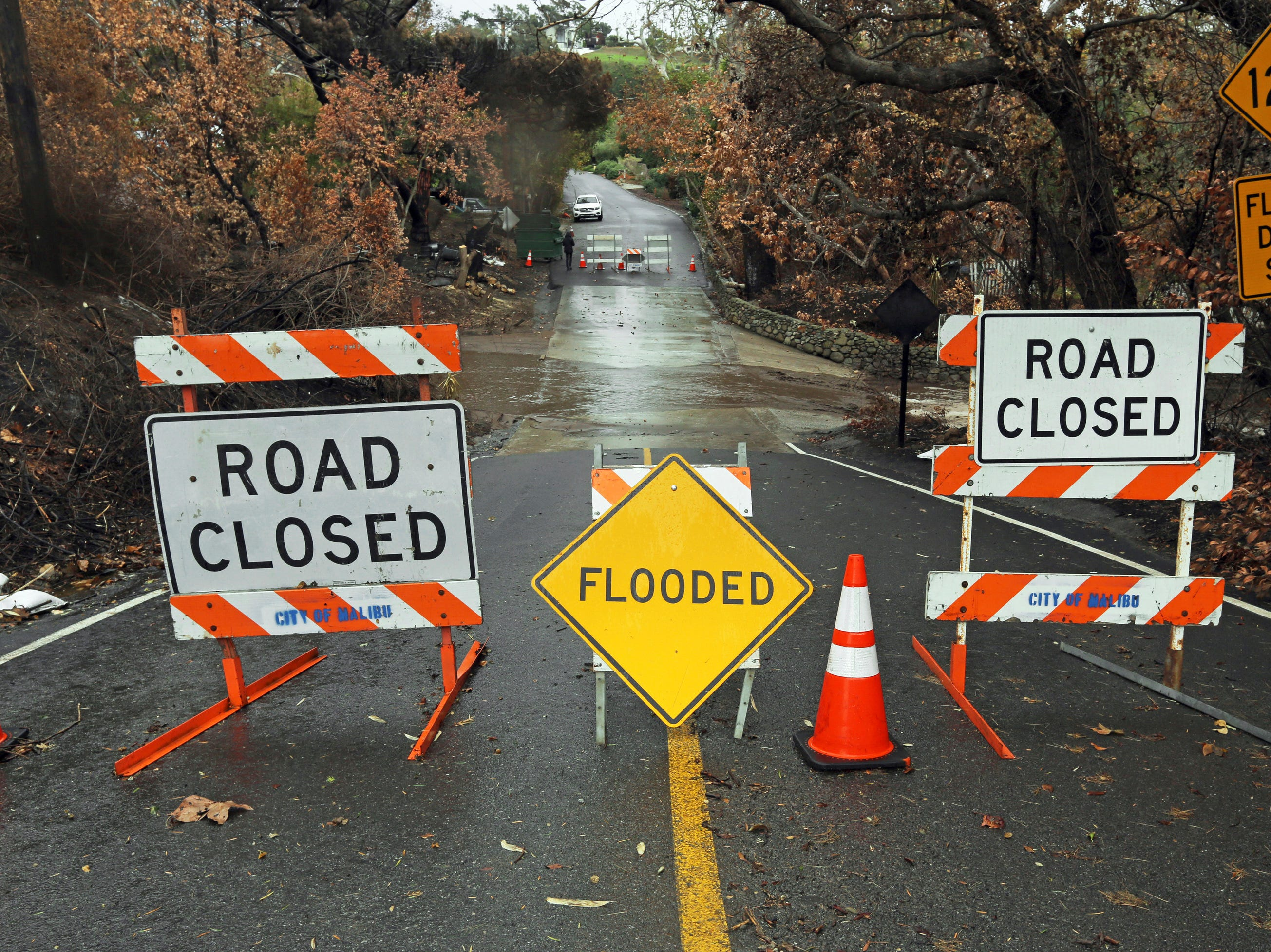 A road is closed due to flooding in an area burned by the Woolsey Fire in Malibu, Calif., Thursday, Dec. 6, 2018.