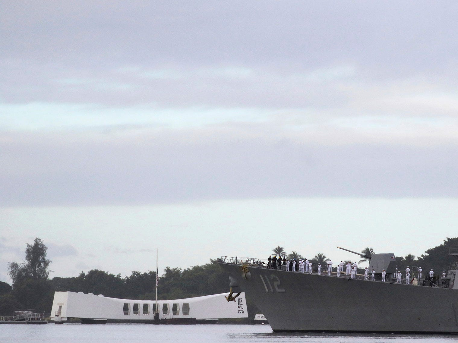 The USS Michael Murphy passes by the USS Arizona Memorial in Pearl Harbor, Hawaii on Friday, Dec. 7, 2018 during a ceremony marking the 77th anniversary of the Japanese attack. The Navy and National Park Service jointly hosted the remembrance ceremony at a grassy site overlooking the water and the USS Arizona Memorial.