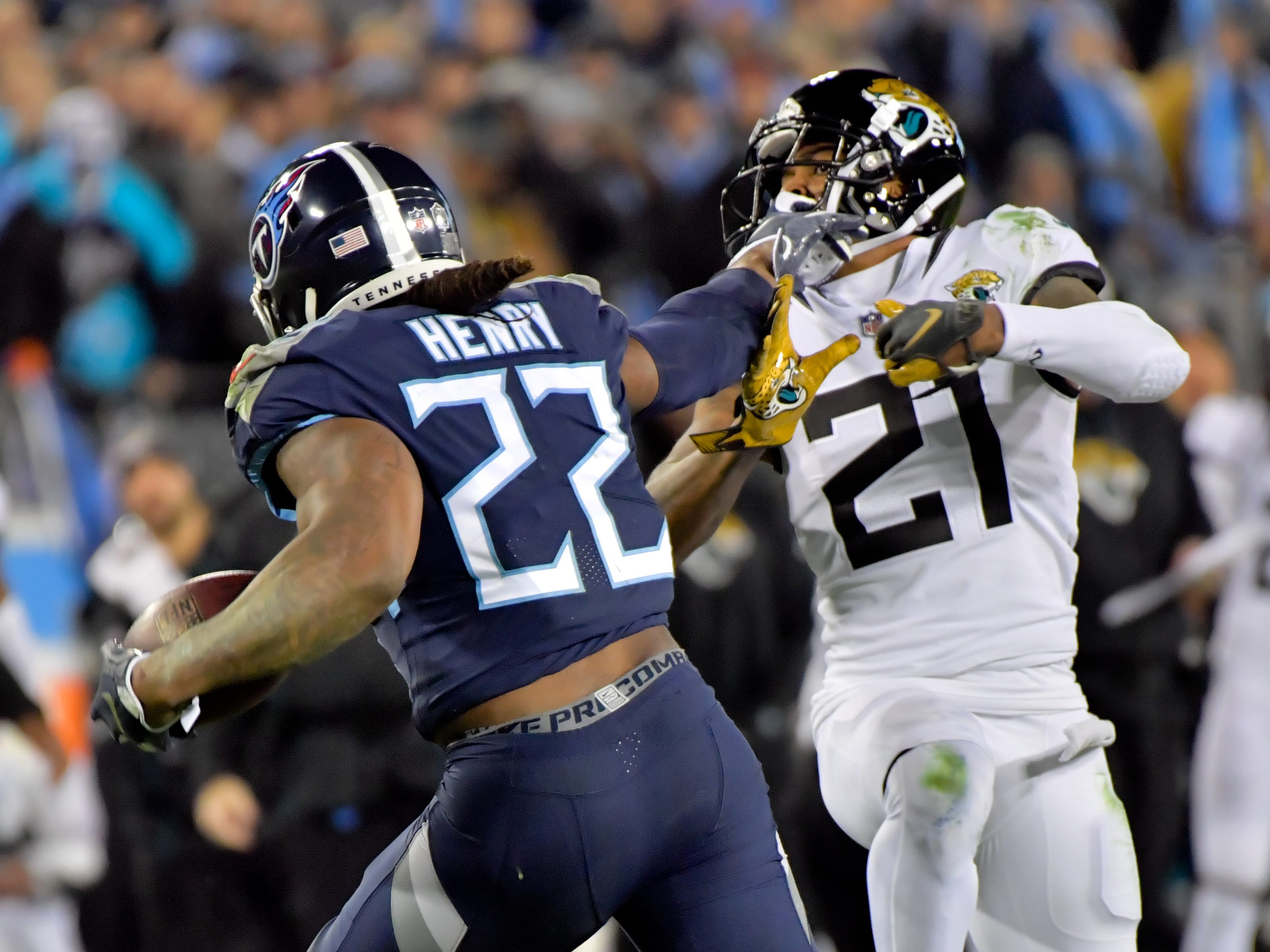 Tennessee Titans running back Derrick Henry (22)  pushes past Jacksonville Jaguars cornerback A.J. Bouye (21) and runs 99 yards for the touchdown during the first half at Nissan Stadium.