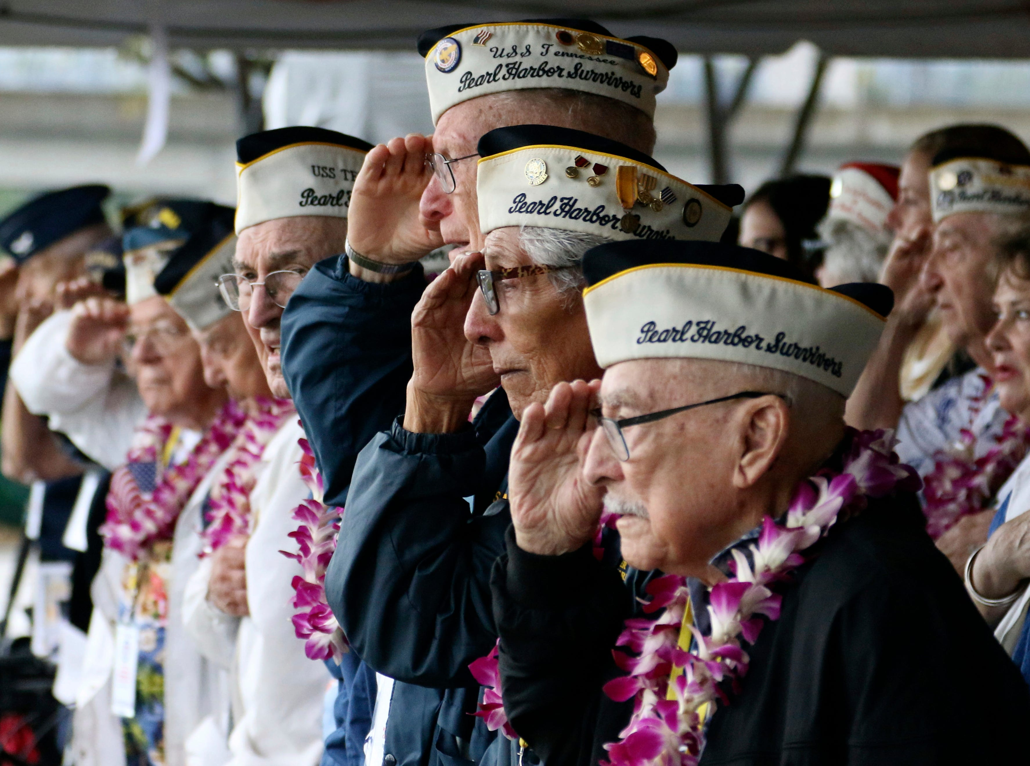 Pearl Harbor survivors salute during the National Anthem at a ceremony in Pearl Harbor, Hawaii on Friday, Dec. 7, 2018 marking the 77th anniversary of the Japanese attack. The Navy and National Park Service jointly hosted the remembrance ceremony at a grassy site overlooking the water and the USS Arizona Memorial.
