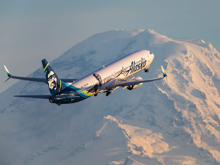 An Alaska Airlines Boeing 737-900 takes off over Mount Rainier from Seattle-Tacoma International Airport in November 2018.