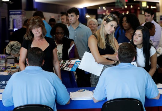 Job applicants are pictured talking with representatives from Aldi at a job fair hosted by Job News South Florida, in Sunrise, Florida.