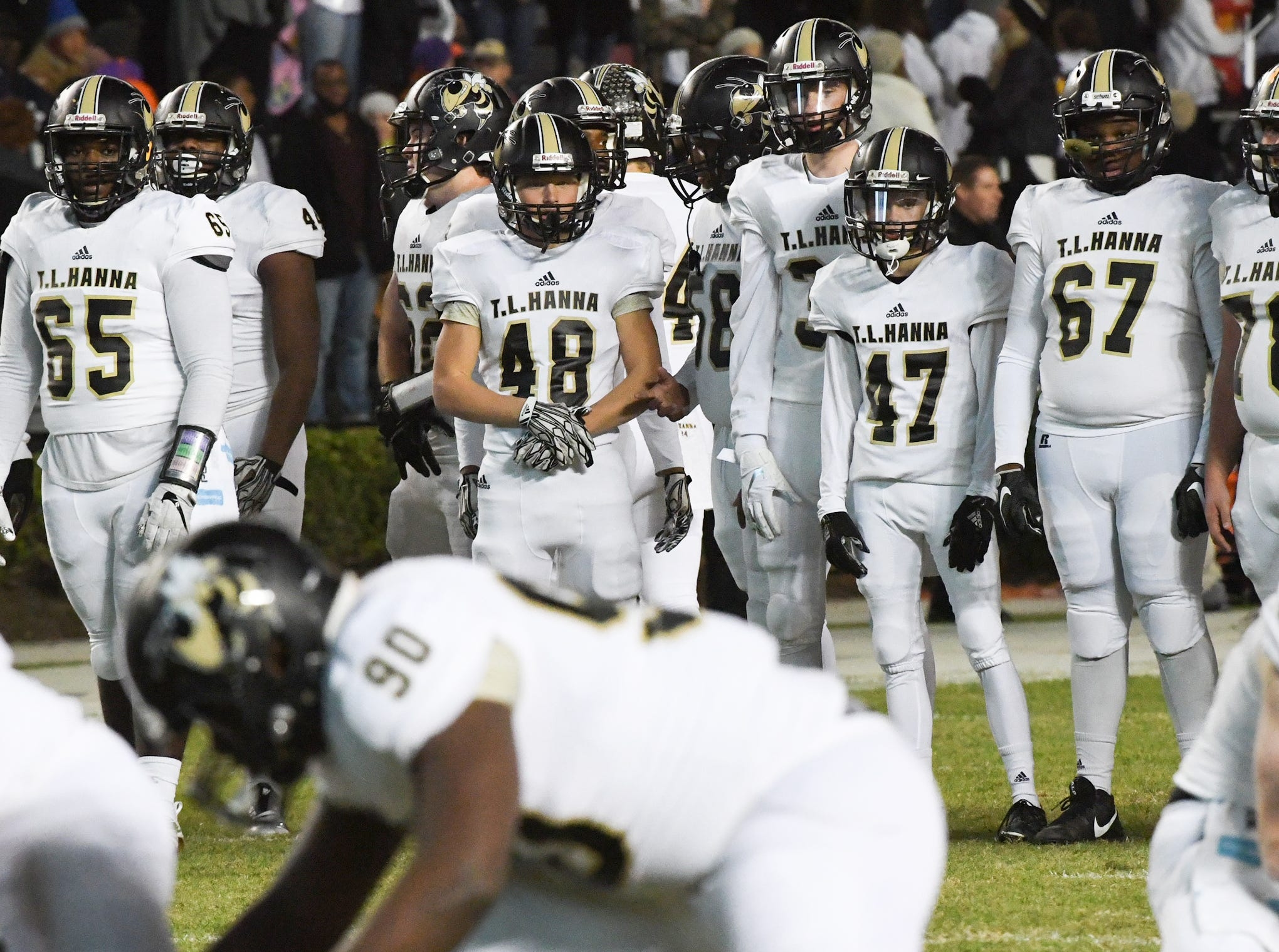 TL Hanna senior Russell Hamby (48), middle, and others watch teammates warm up before the kickoff of the Class AAAAA state championship game at Williams-Brice Stadium in Columbia Saturday, December 8, 2018.