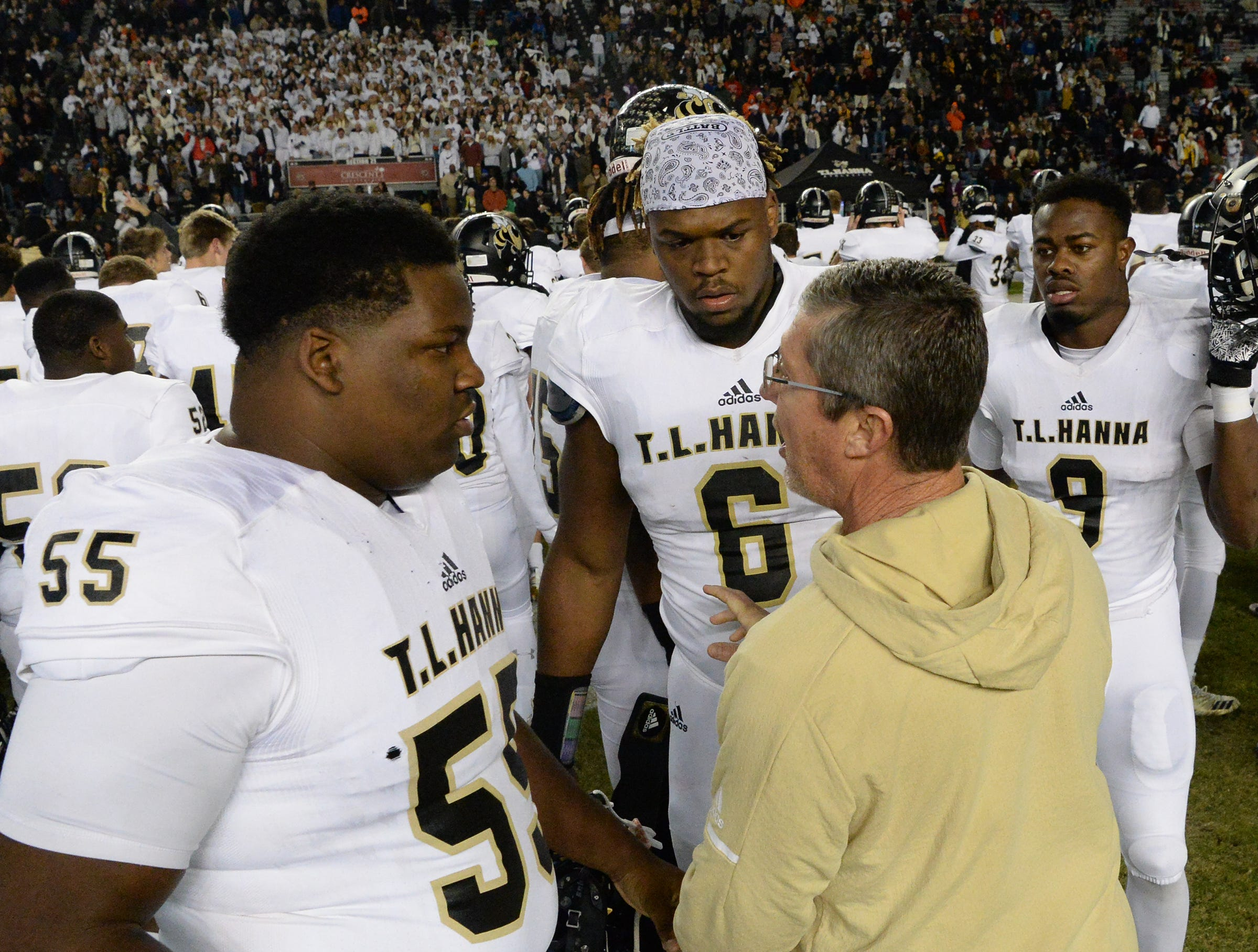 TL Hanna senior Devonte Jones (55) and TL Hanna senior Zacch Pickens (6) listen to TL Hanna head coach Jeff Herron before the kickoff of the Class AAAAA state championship game at Williams-Brice Stadium in Columbia Saturday, December 8, 2018.