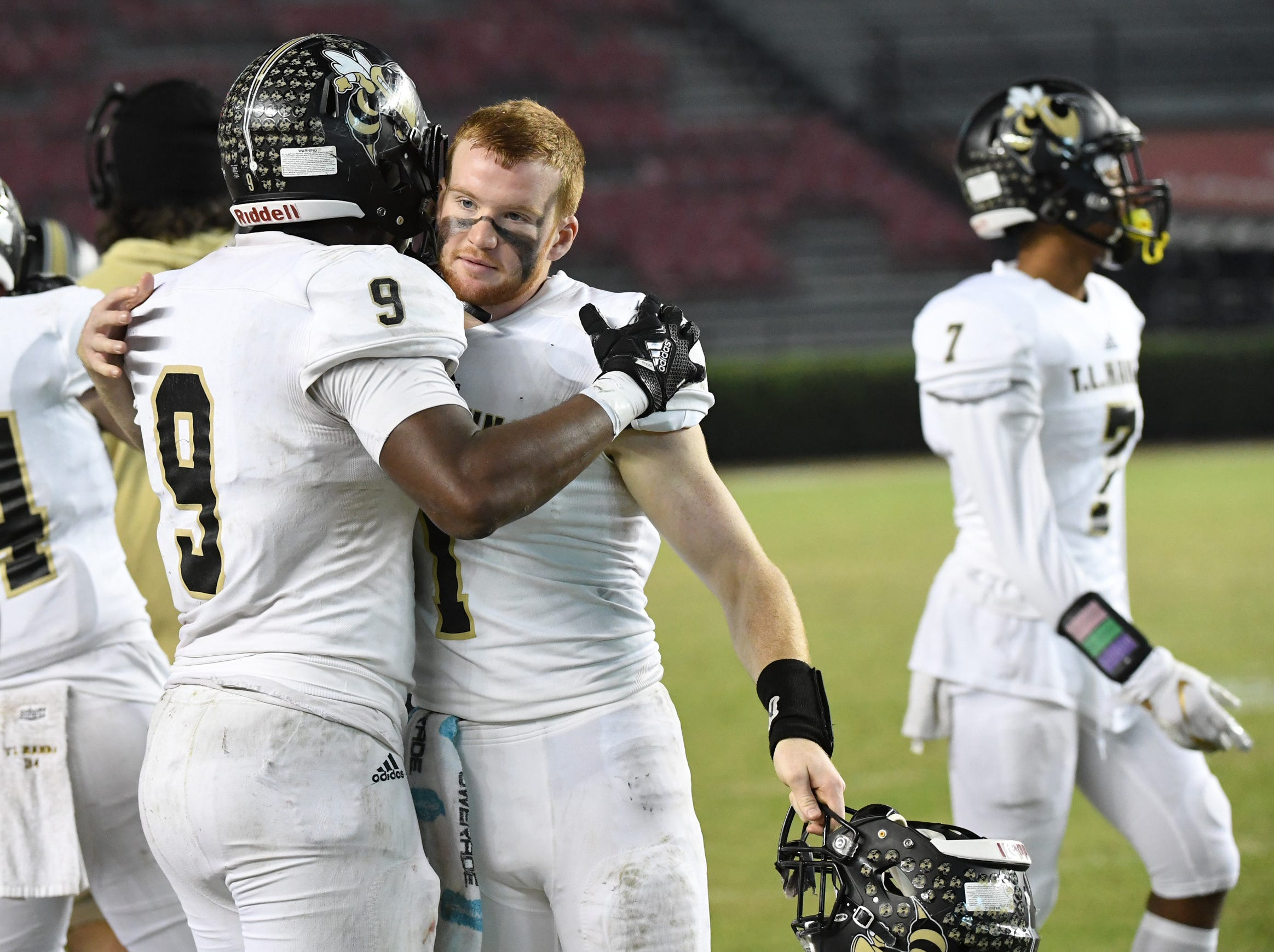 TL Hanna senior Jay Lagroon (9) and TL Hanna senior Alex Meredith (1) hug in the closing seconds during the fourth quarter of the Class AAAAA state championship game at Williams-Brice Stadium in Columbia Saturday, December 8, 2018.
