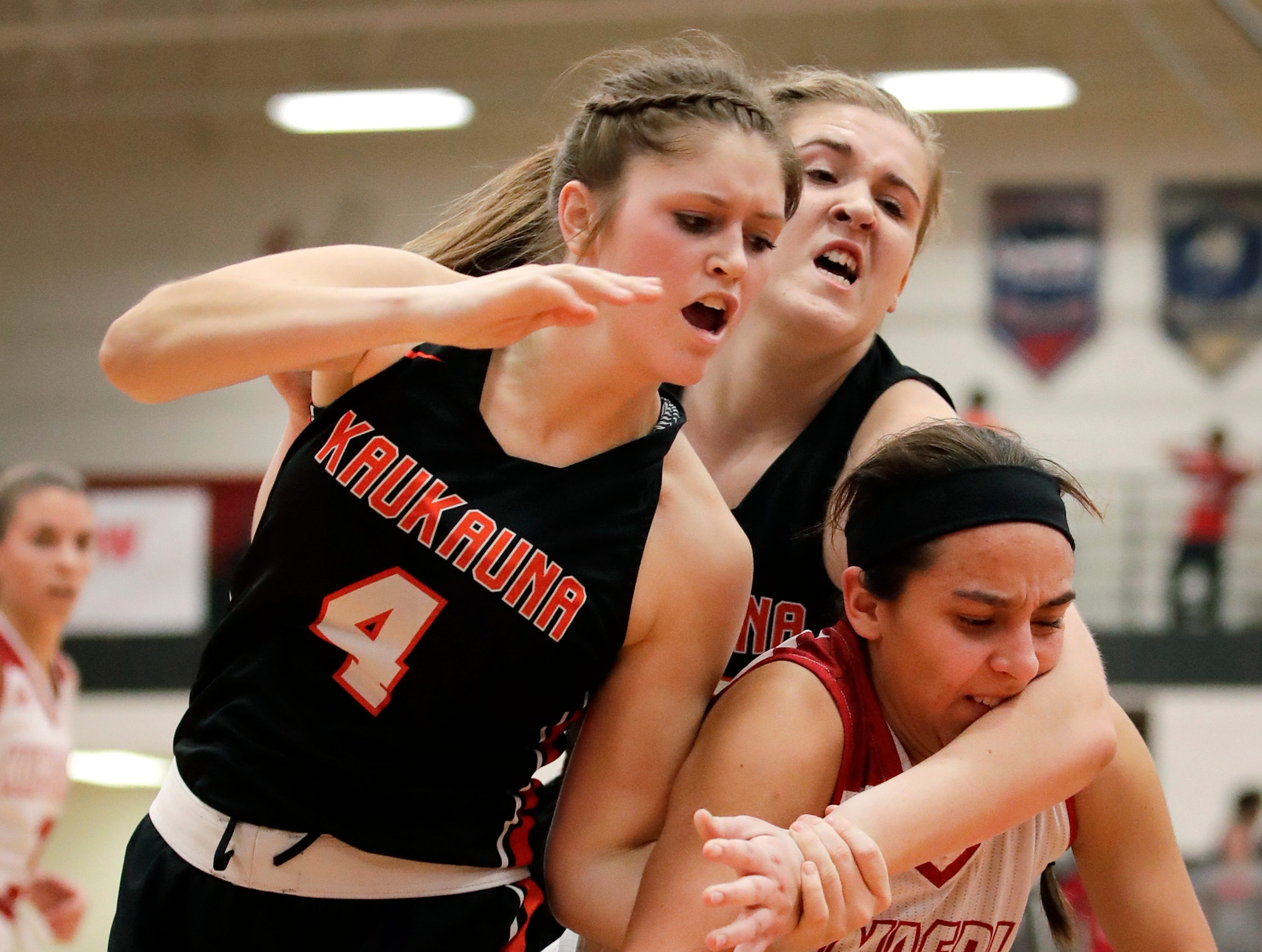 Kaukauna High School's Graysin Hinkens and Madison Herdina get tangled with Kimberly High School's Shea Dechant while going for a rebound Friday, Dec. 7, 2018, in Kimberly, Wis. Kimberly High School defeated Kaukauna High School 70-55.