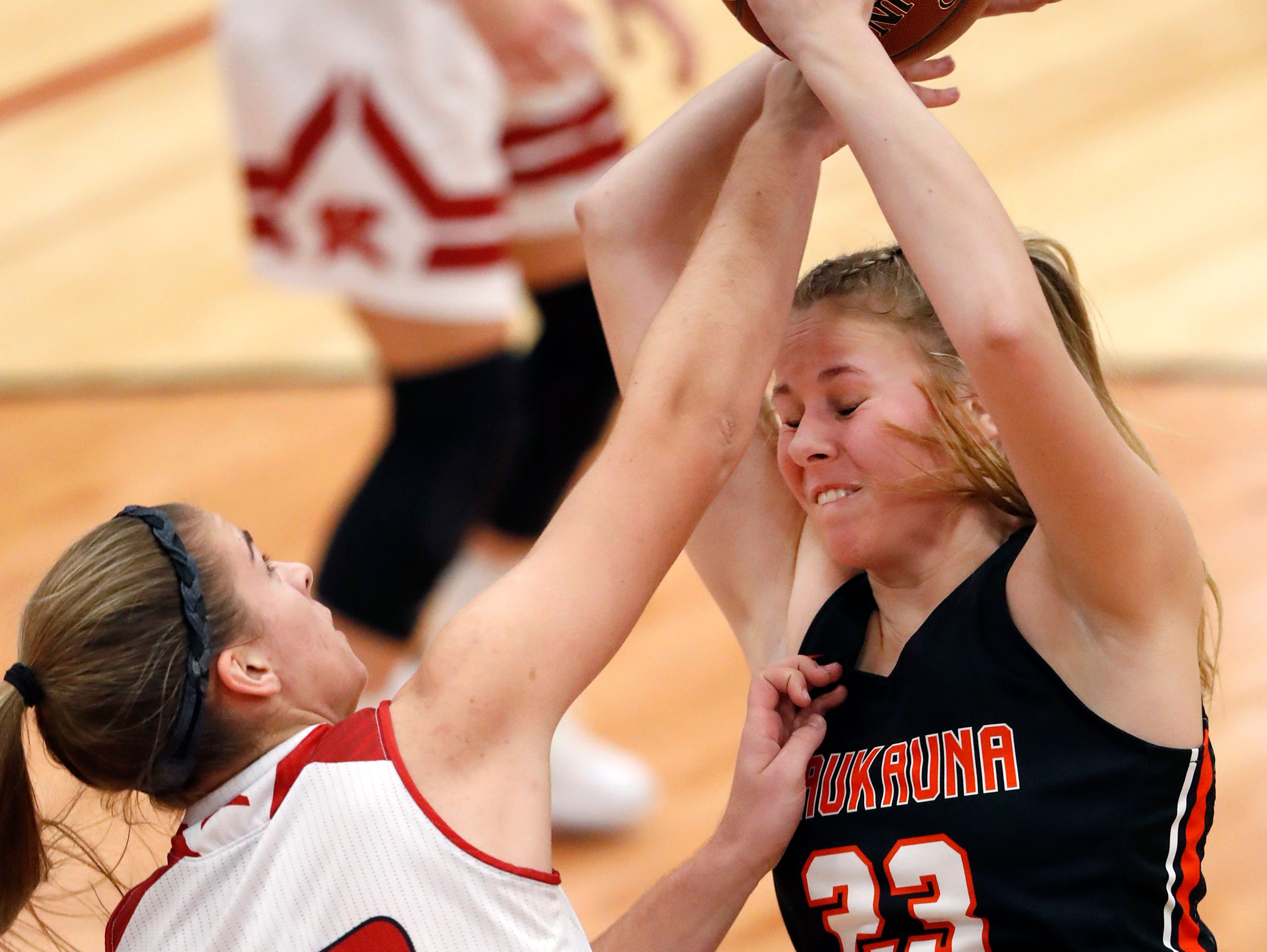 Kimberly High School's Marissa Murray and Kaukauna High School's Avery Torrey go for a rebound Friday, Dec. 7, 2018, in Kimberly, Wis.