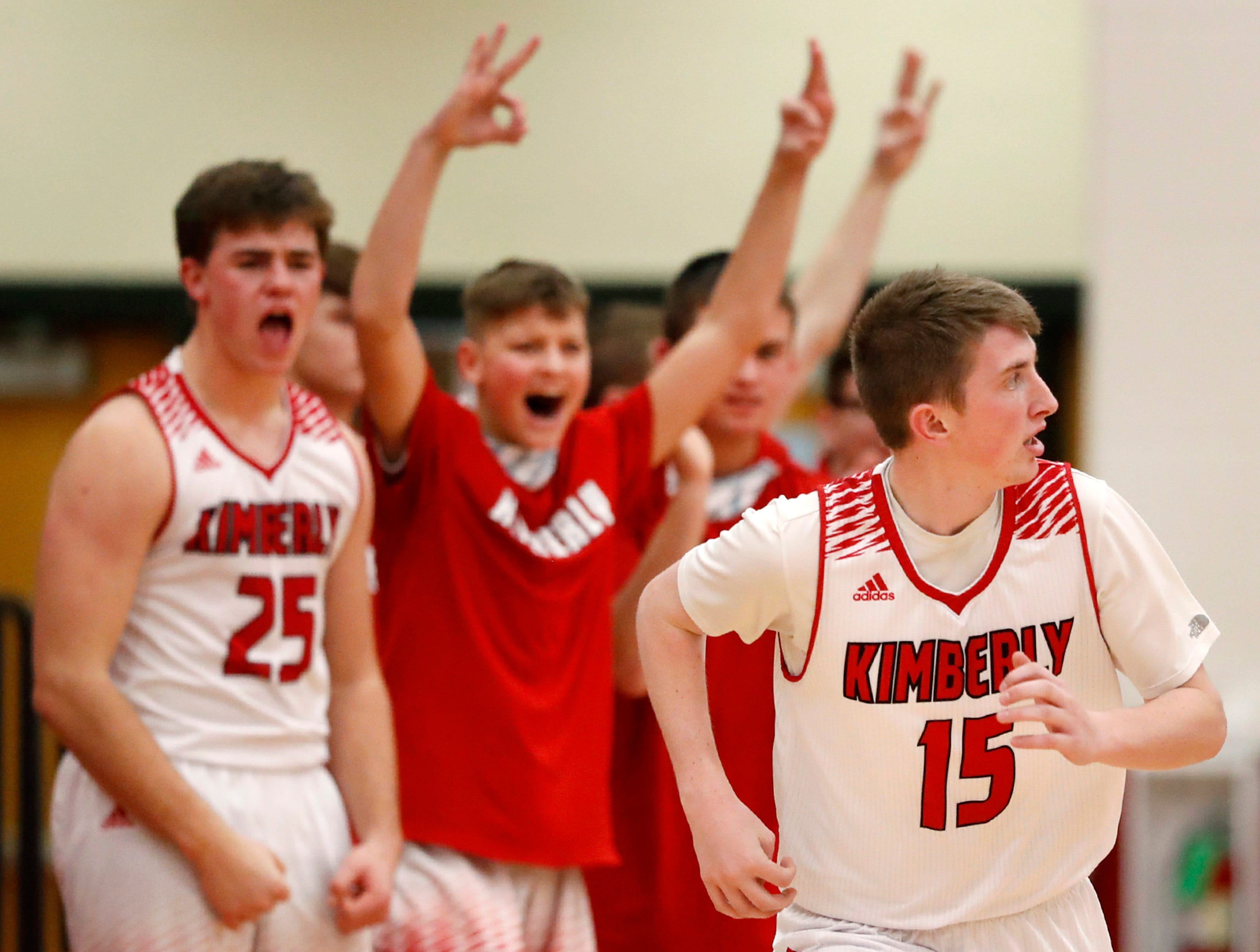 Teammates celebrate a three-point basket by Kimberly High School's Charlie Jacobson during their game against Kaukauna High School Friday, Dec. 7, 2018, in Kimberly, Wis.
