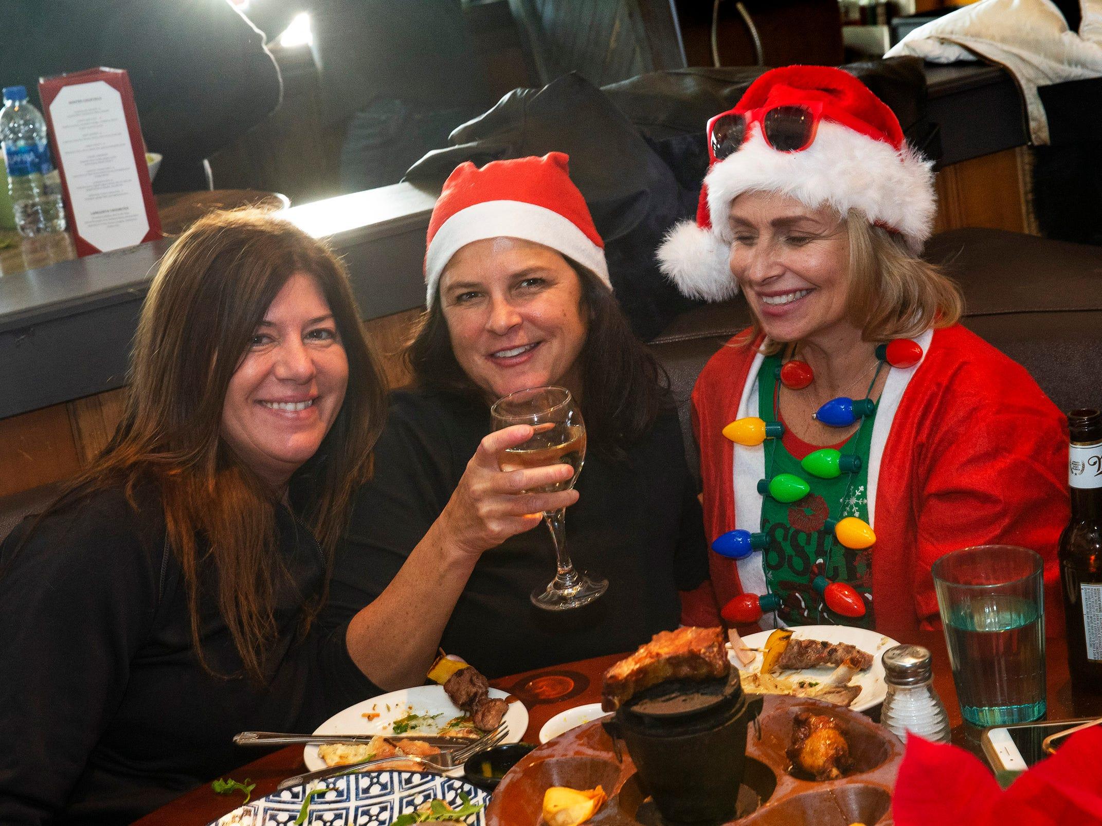 Lisa Theodore and Kim Lamberto of Oceanport and Deborah Zito of Eatontown enjoy a meal and drinks  at the Langosta Lounge during SantaCon Bar Crawl through Asbury Park on December 8, 2018.