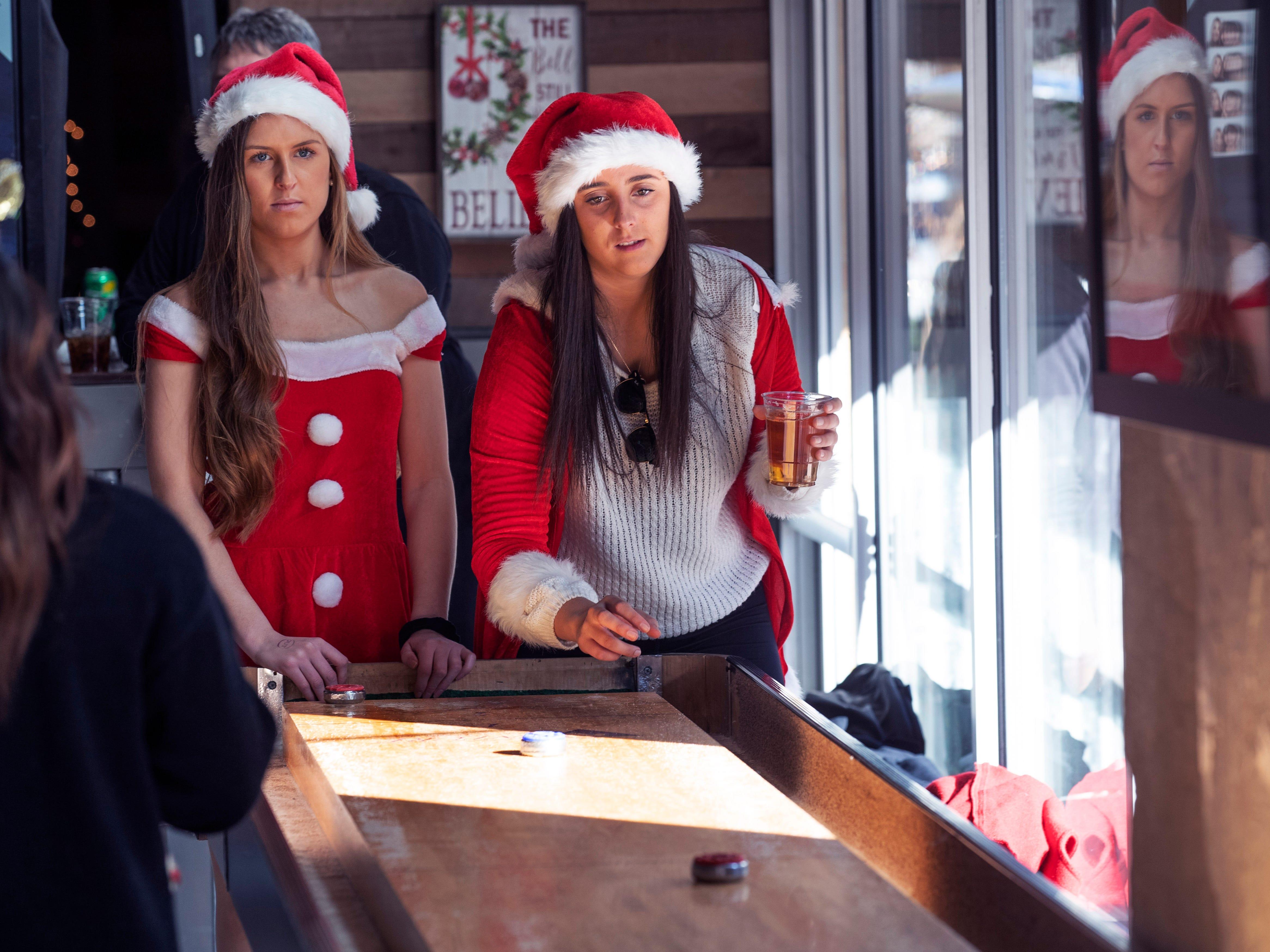 Veronica Lane and Katie Foley, both Monmouth University students enjoy the SantaCon Bar Crawl through Asbury Park on December 8, 2018 as they visit Asbury Ale House.