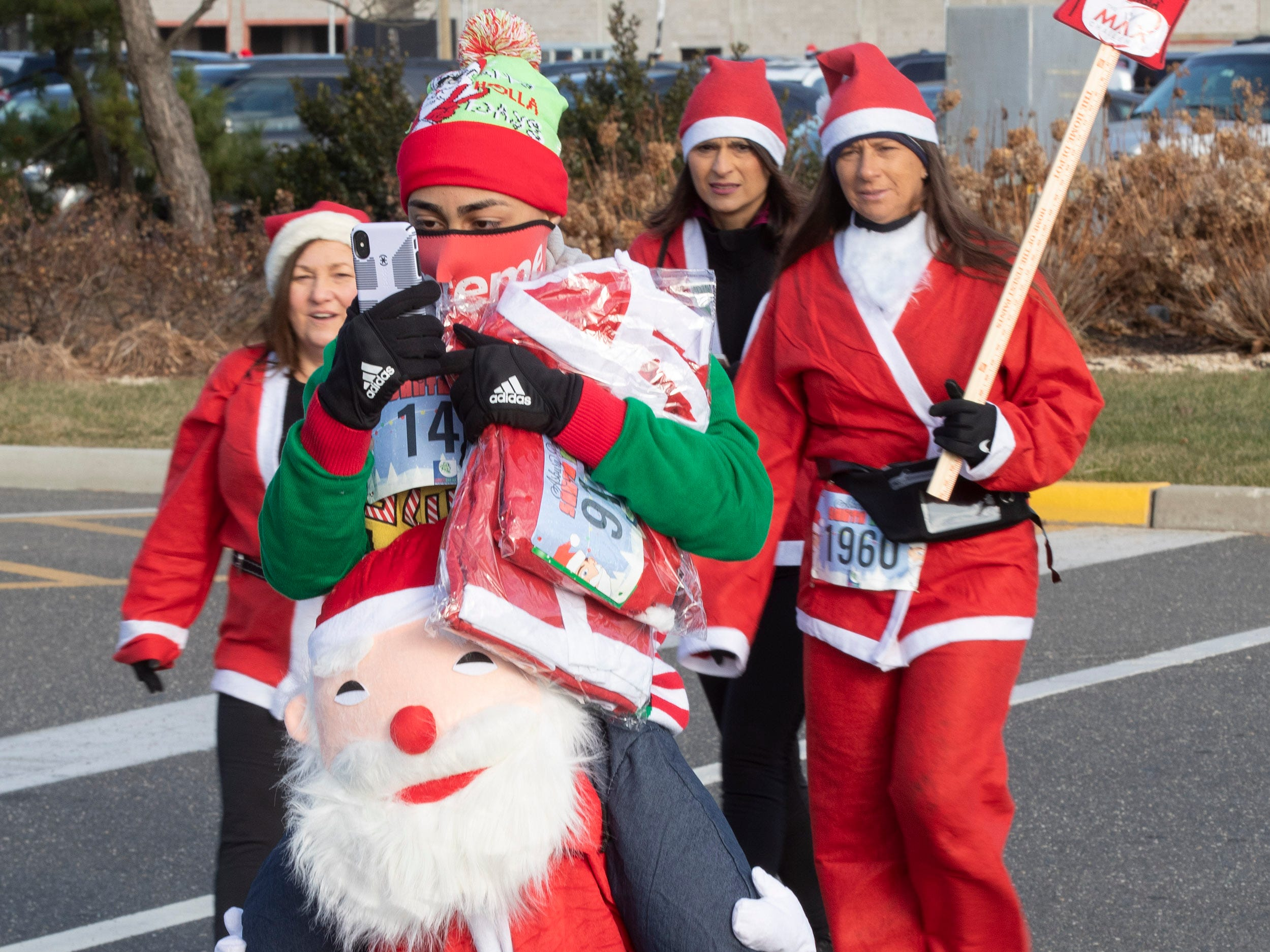 Victor Bosque of Old Bridge runs as two Santas. Runners brave the cold to participate in the annual Santa Run 5K in Asbury Park on December 8, 2018.