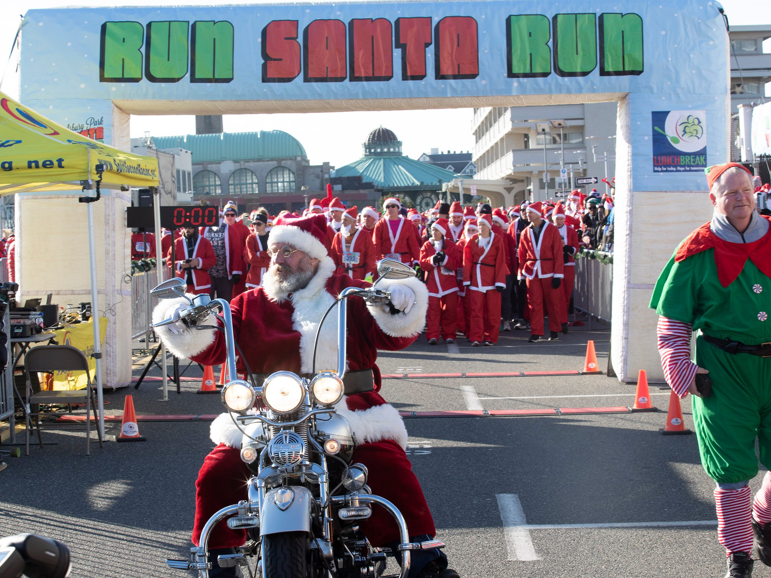 Brian Sheehy of Colts Neck lead the race on motorcycle. Runners brave the cold to participate in the annual Santa Run 5K in Asbury Park on December 8, 2018.