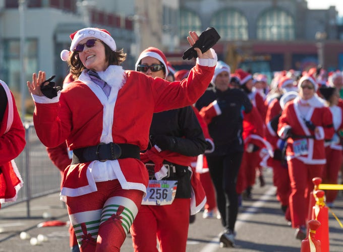 One runner seems happy about her efforts as she starts the second lap. Runners brave the cold to participate in the annual Santa Run 5K in Asbury Park on December 8, 2018.