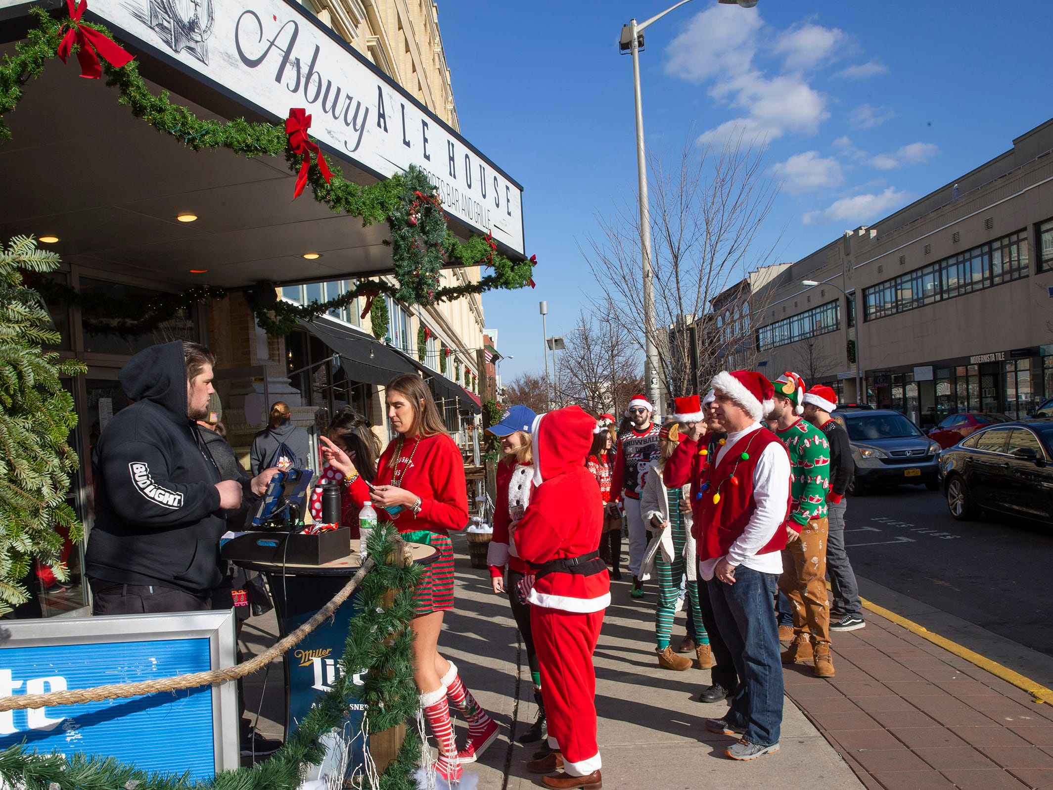 Patrons line up to buy tickets to SantaCon Bar Crawl at the Asbury Ale House in Asbury Park on December 8, 2018.