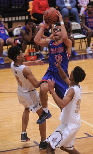 Cooper's Ben Thompson, center, drives between two Fort Worth Chisholm Trail defenders. Chisholm Trail beat the Cougars 64-62 in pool play at the Catclaw Classic at Wylie's Bulldog Gym.