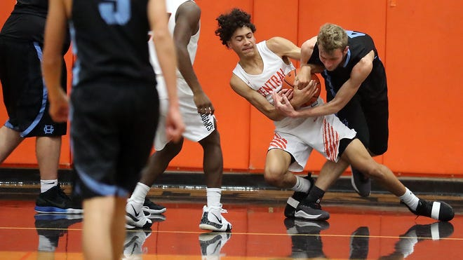 Owen Davies of Central Kitsap fights for possession with Braxton Porter of Gig Harbor during a Dec. 7 game in Silverdale. The Cougars won, 56-46, and are 5-1 on the season.