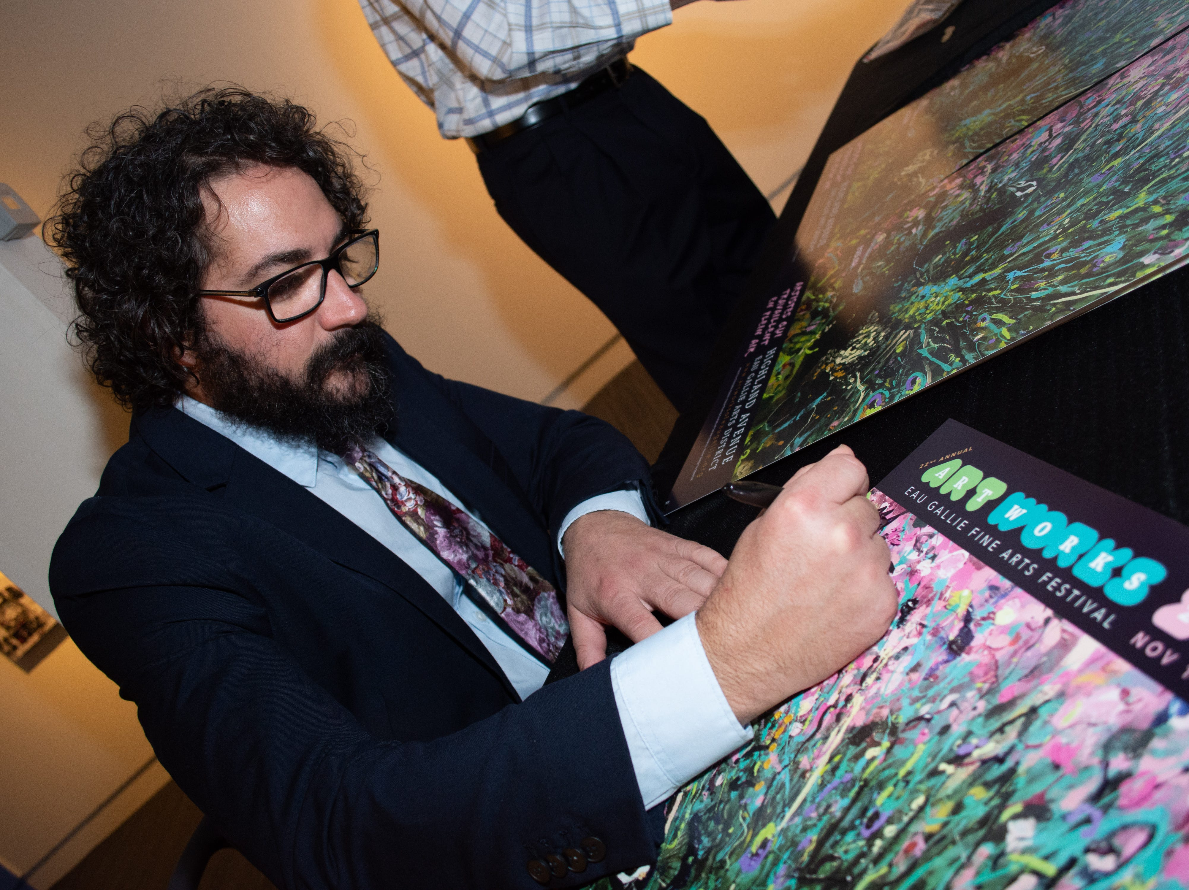 The 2018 Artworks poster artist Christopher Maslow signs his work for a sponsor.