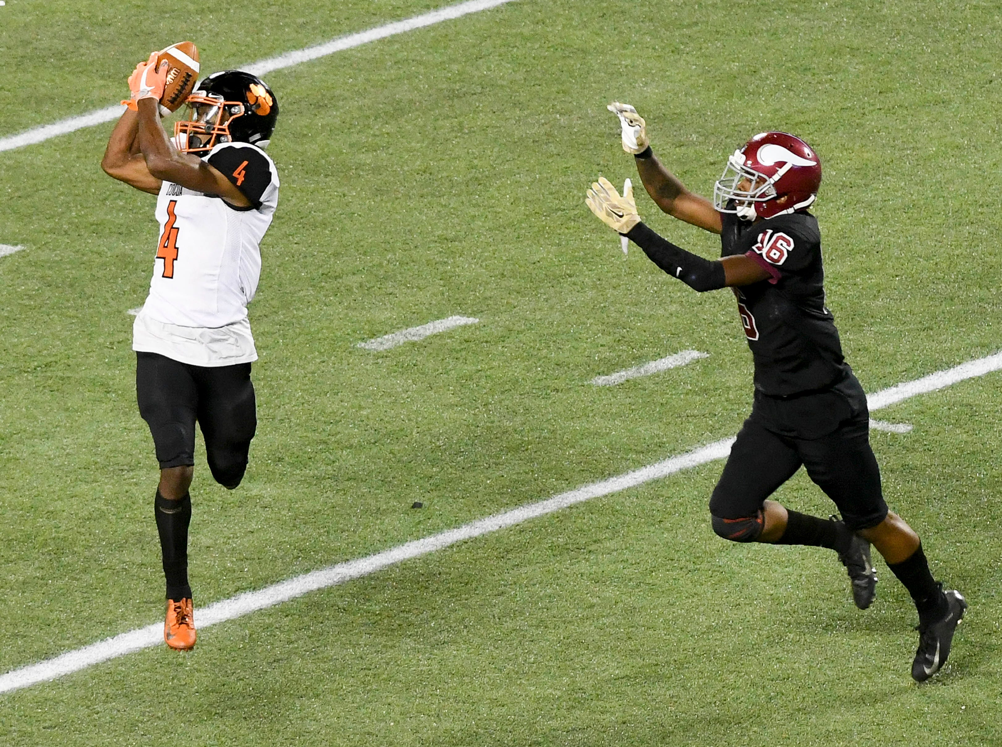 Willie Gaines of Cocoa catches a pass in front of Raines defender James Tarver, Jr. during Thursday's Class 4A football state championship.