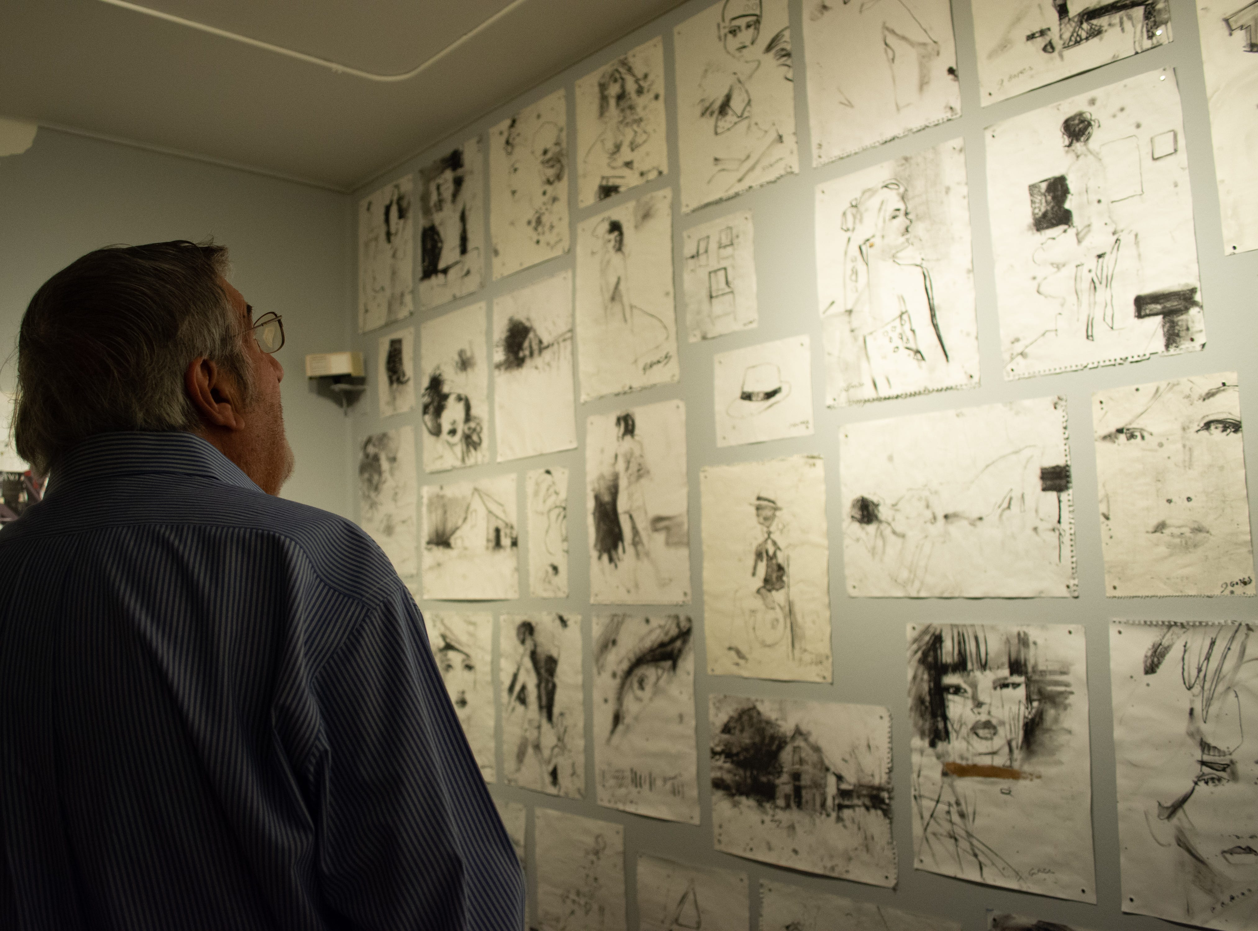 Tony Alonso takes a look at the wall of wet paintings.