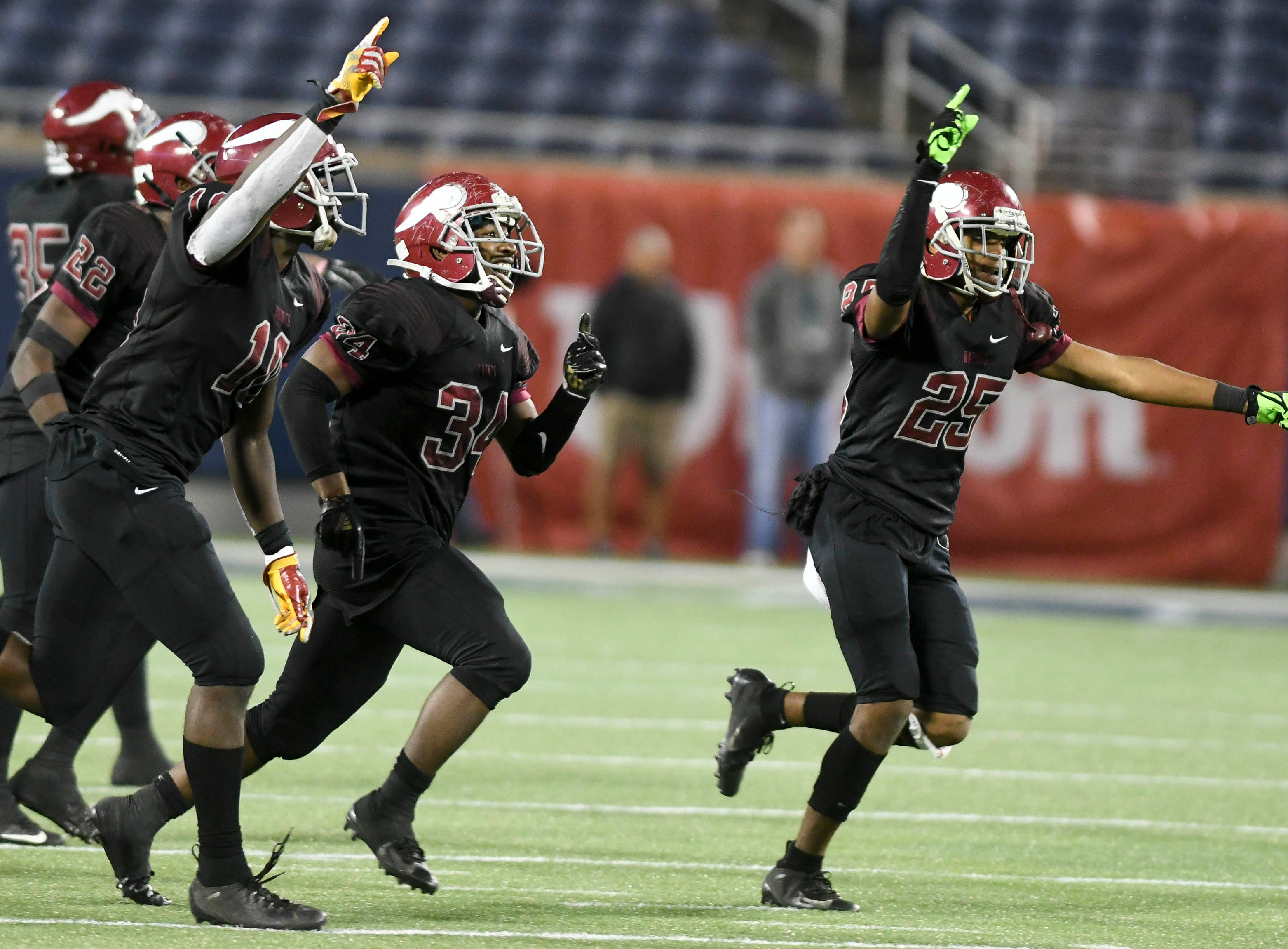 Raines players celebrate after interception a Cocoa pass during Thursday's Class 4A football state championship.