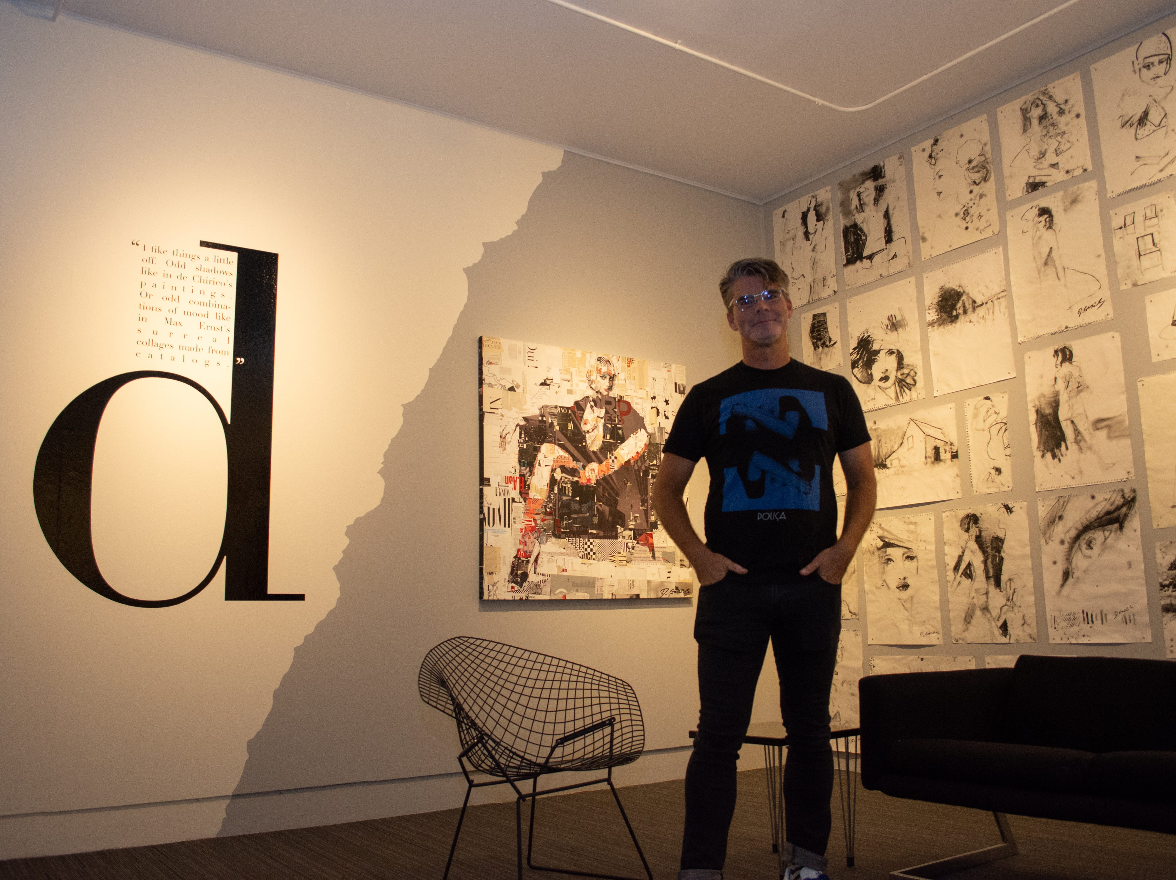 Artist Derek Gores poses for a photo in front of his Animal Pragmatism collage.