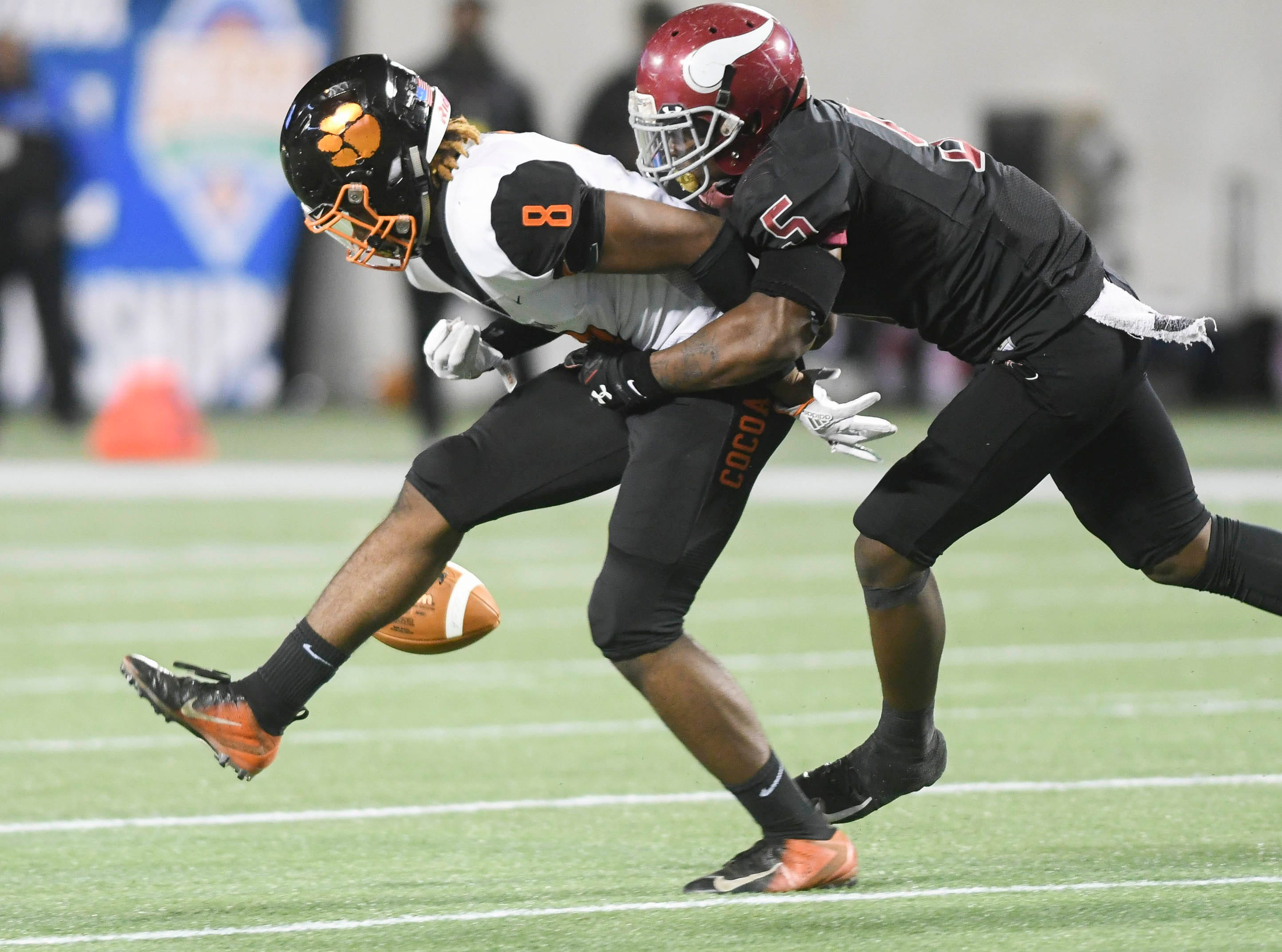 Javon Bonsell of Raines (5) forces Caziah Holmes of Cocoa to fumble the ball during Thursday's Class 4A football state championship.