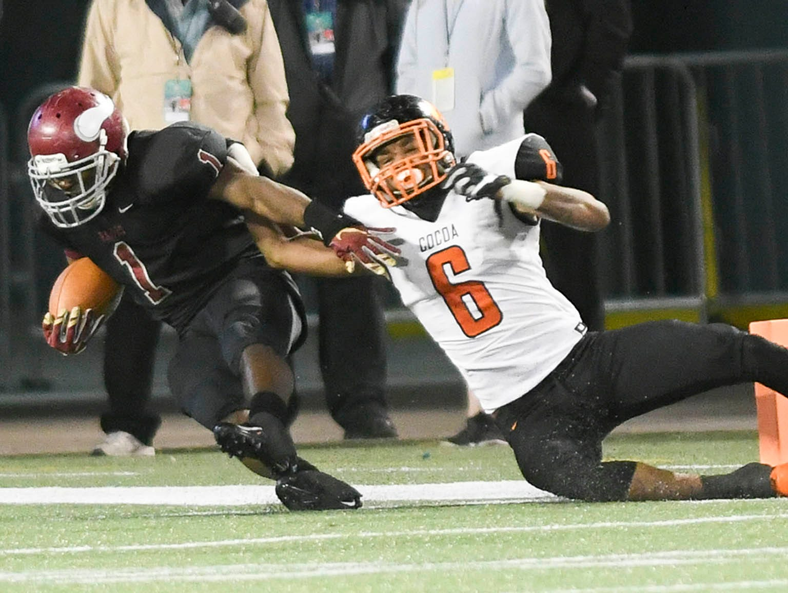 Cocoa's Tyrique Sears drags down Brandon Marshall of Raines as he scores a touchdown in Thursday's Class 4A football state championship.
