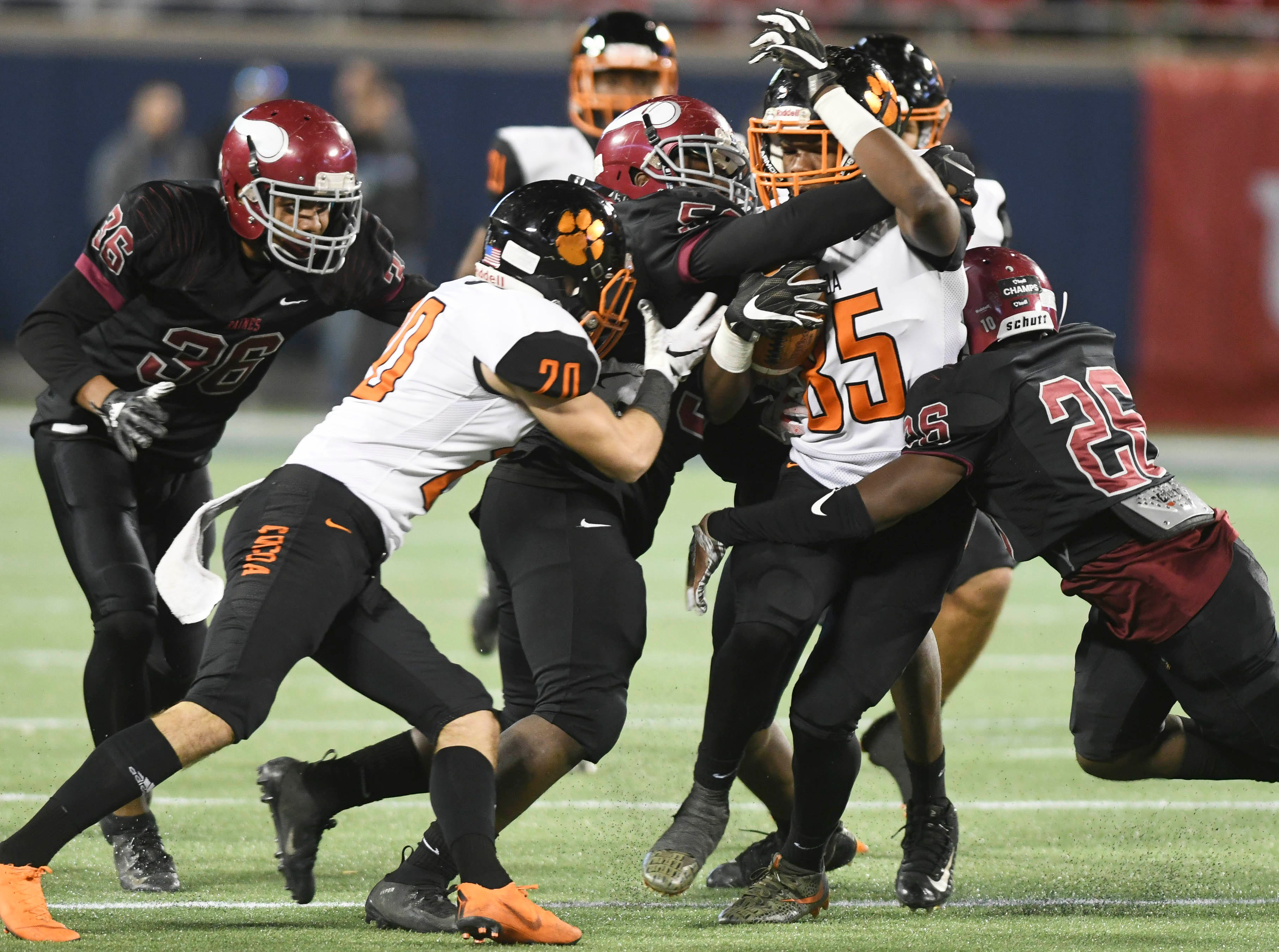Cocoa's Demarquez Henley of Cocoa (85) struggles for yardage during Thursday's Class 4A football state championship. On the tackle for Raines is Adrien Tarver (26) Kyree Hammond (36) and Reginald Harden (46).