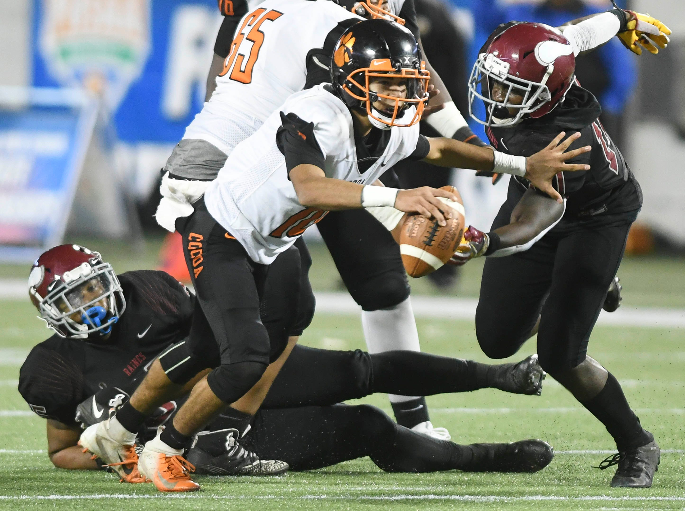 Cocoa QB Diego Arroyo is sacked by Aric Horne and Jaren Wilson of Raines during Thursday's Class 4A football state championship.