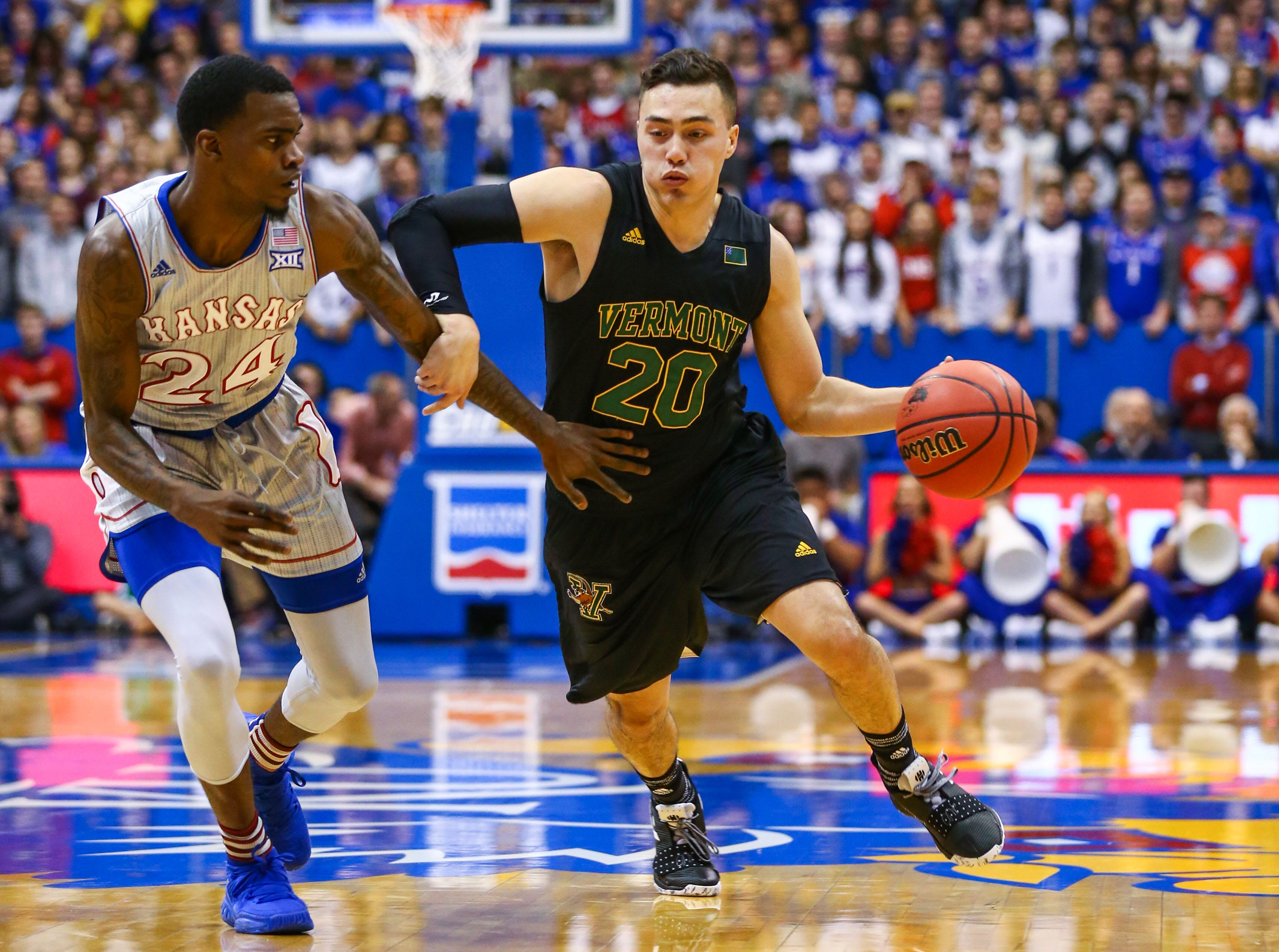 Vermont Catamounts guard Ernie Duncan (20) dribbles the ball against Kansas Jayhawks guard Lagerald Vick (24) in the first half at Allen Fieldhouse.