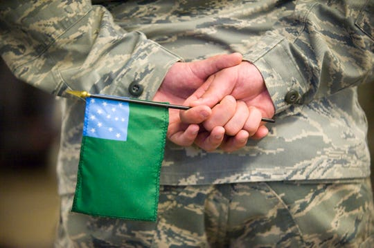 An airman holds a Green Mountain battle flag during a deployment ceremony for a group of airmen from the Vermont Air National Guard 158th fighter wing headed to Saudi Arabia in South Burlington on Thursday April 8, 2010.