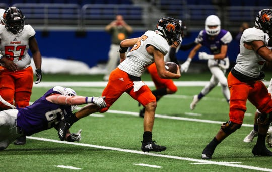 Refugio's Austin Ochoa tries to break free of Mason's defense during Friday's Class 2A Division I state quarterfinal playoff game at the Alamodome.