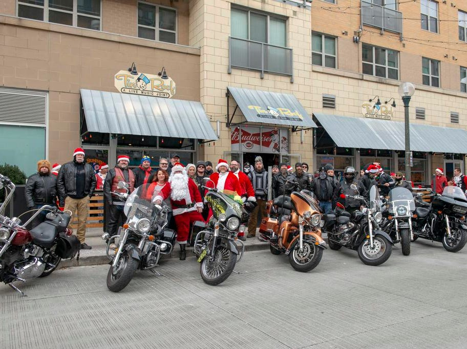 Cincinnati SantaCon 2018 brought hundreds of people dressed as Santa Claus and other Christmas characters to The Banks to spread good cheer and charity.  Santa digs Harleys