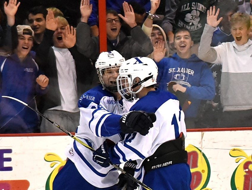 Jake Anding and Nick Langenderfer of St. Xavier celebrate their game-tying goal  against Moeller at US Bank Arena, December 7, 2018.