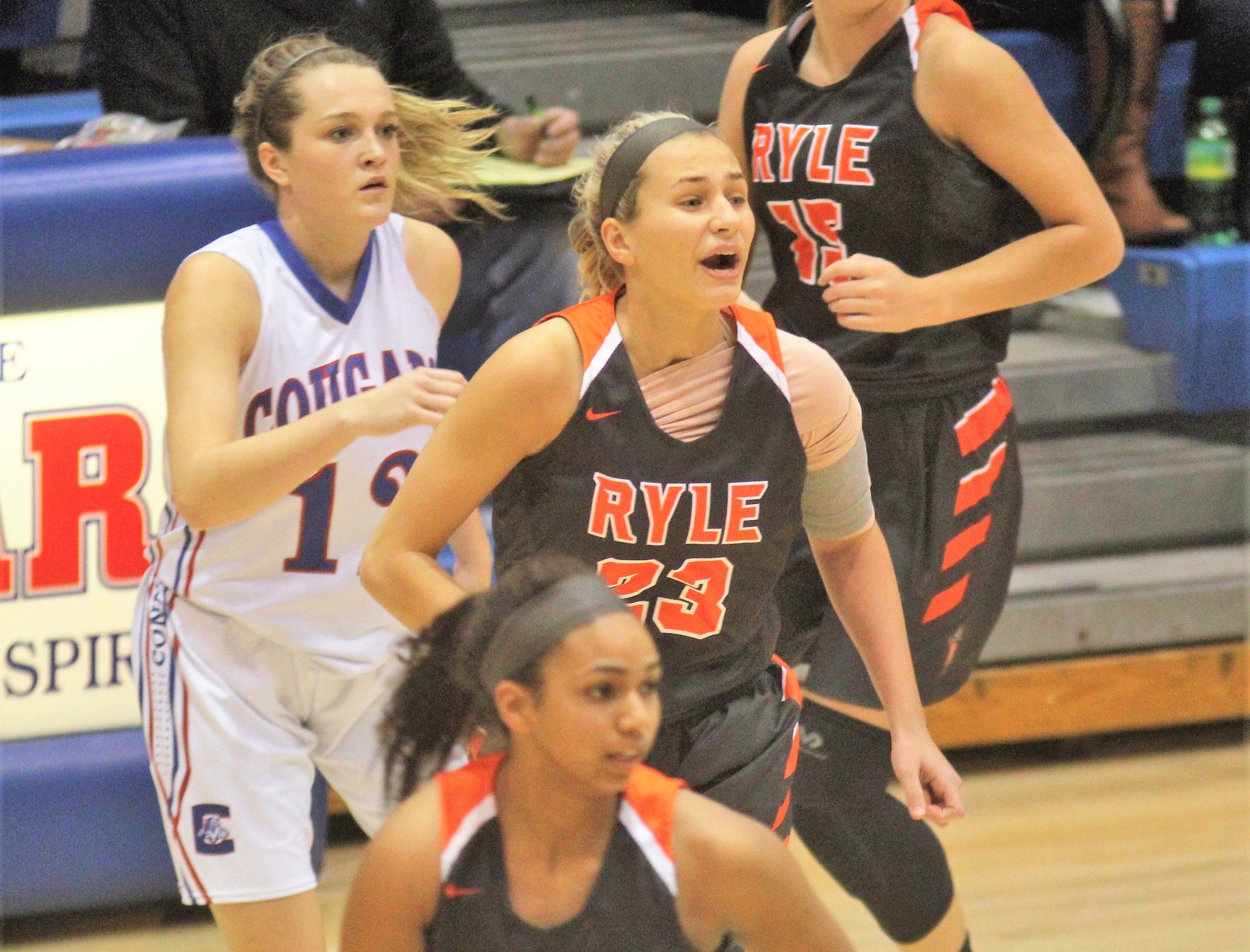 Conner senior Courtney Hurst, 12, and Ryle junior Maddie Scherr, 23, look for the ball as Ryle defeated Conner 60-49 in a girls basketball district game Dec. 7, 2018 at Conner High School, Hebron KY.