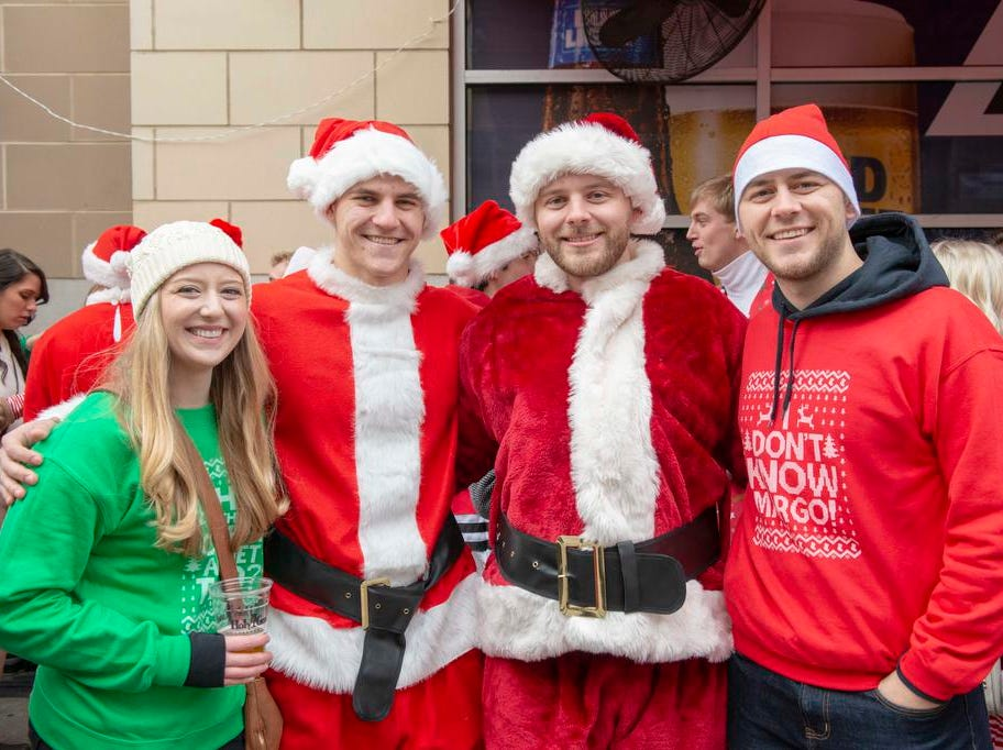 Cincinnati SantaCon 2018 brought hundreds of people dressed as Santa Claus and other Christmas characters to The Banks to spread good cheer and charity. Hannah Brown, Danny Ley, Andrew McDarty andd Joe Brown.