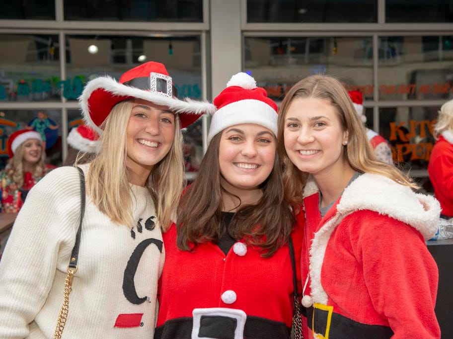 Cincinnati SantaCon 2018 brought hundreds of people dressed as Santa Claus and other Christmas characters to The Banks to spread good cheer and charity.  Sara Ritze, Madison Barga and Anya Jolicoeur.