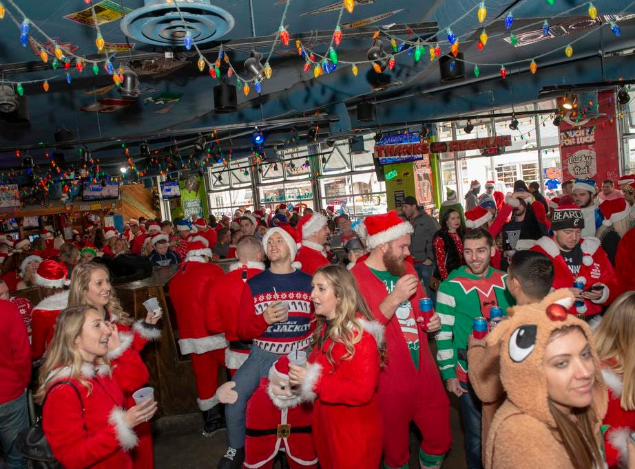 Cincinnati SantaCon 2018 brought hundreds of people dressed as Santa Claus and other Christmas characters to The Banks to spread good cheer and charity. The large crowd inside the Tin Roof bar.