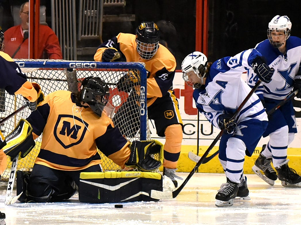Alex Hill (33) tries to push in a shot on goal past Moeller goalie Owen Lundy at US Bank Arena, December 7, 2018.