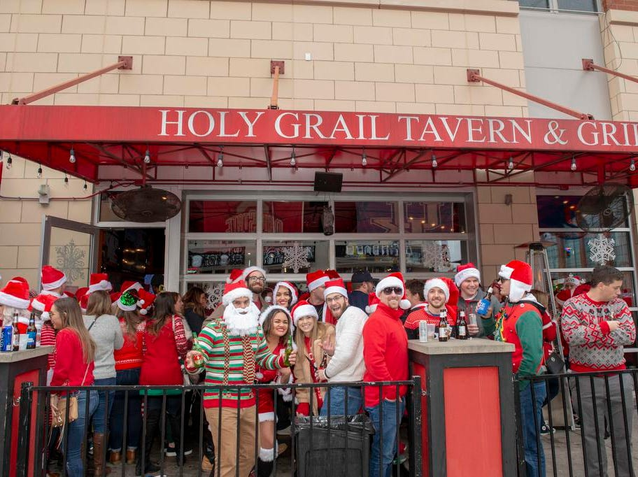 Cincinnati SantaCon 2018 brought hundreds of people dressed as Santa Claus and other Christmas characters to The Banks to spread good cheer and charity. The crowd outside The Holy Grail.