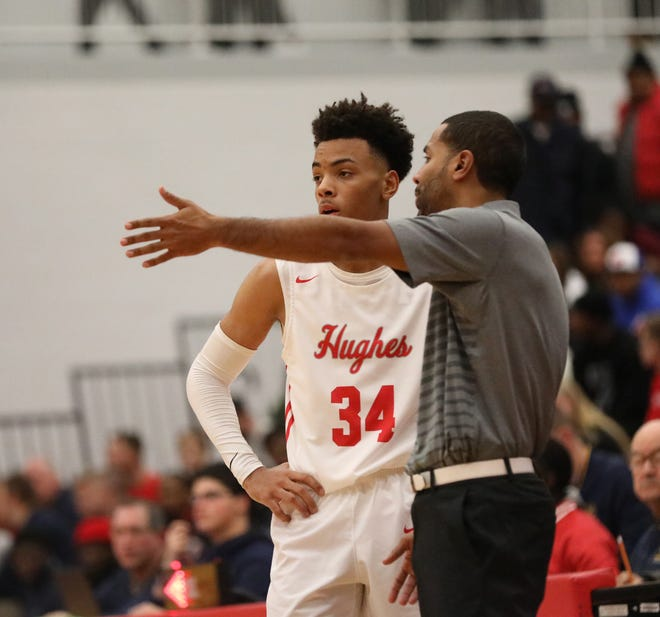Hughes guard Paul McMillan talks with head coach Bryan Wyant during their basketball game against Moeller, Friday, Dec. 7, 2018.