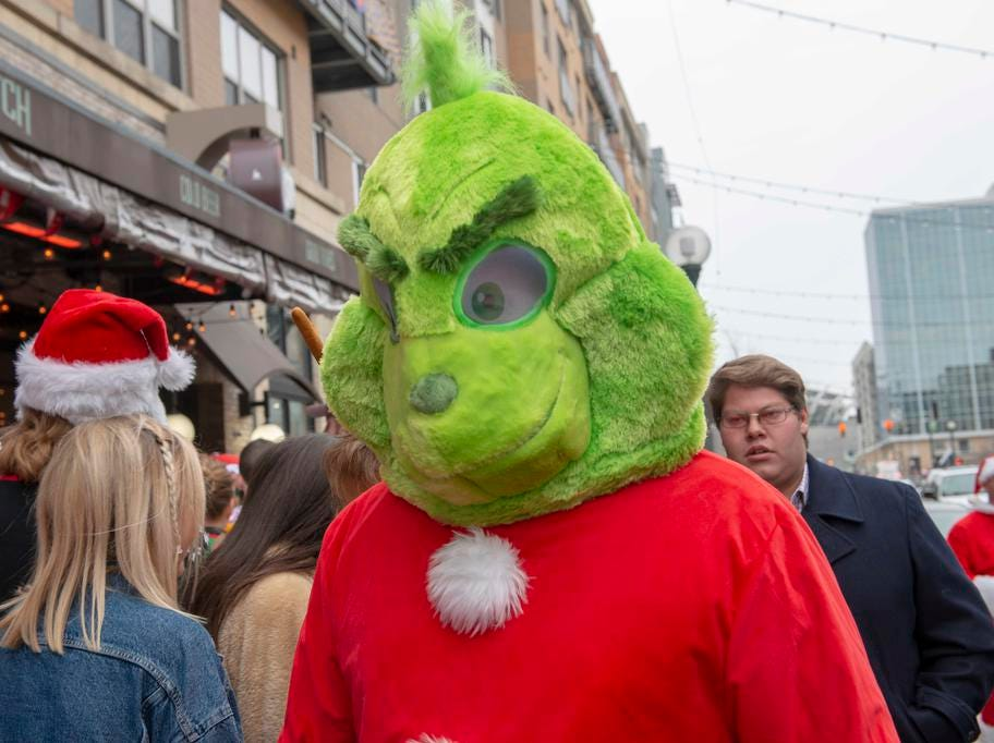 Cincinnati SantaCon 2018 brought hundreds of people dressed as Santa Claus and other Christmas characters to The Banks to spread good cheer and charity. The Grinch makes his way down Freedom Way.